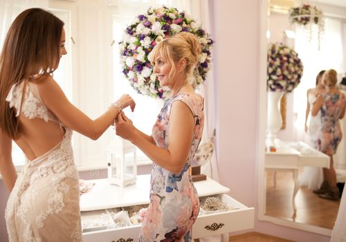 Bride in a wedding dress and her mom getting ready