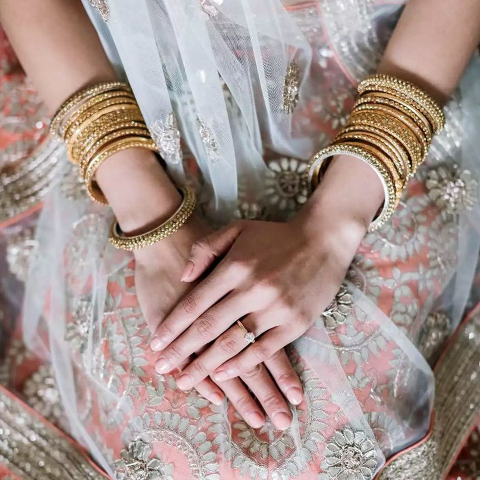Bride wearing bangles and ornate gown with nude colored nail polish