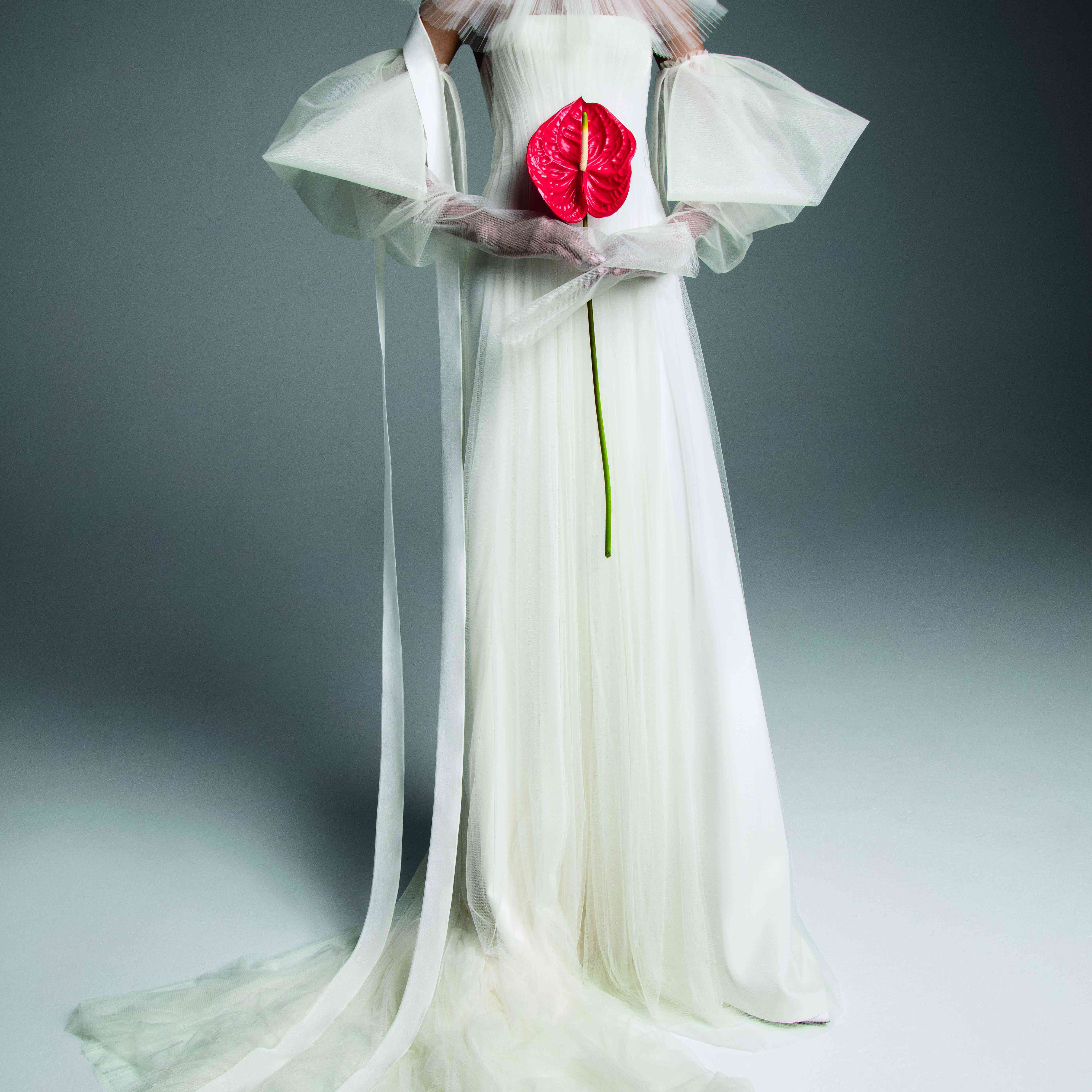 Model in strapless white tulle A-line gown with dramatic detached sleeves