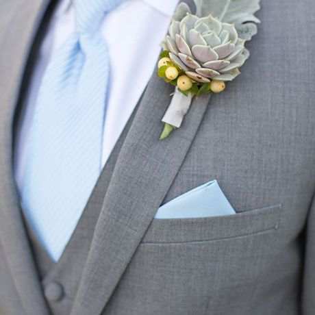 A succulent boutonniere, accent with snowberries and dusty miller leafs, created by Designs by Jeremiah