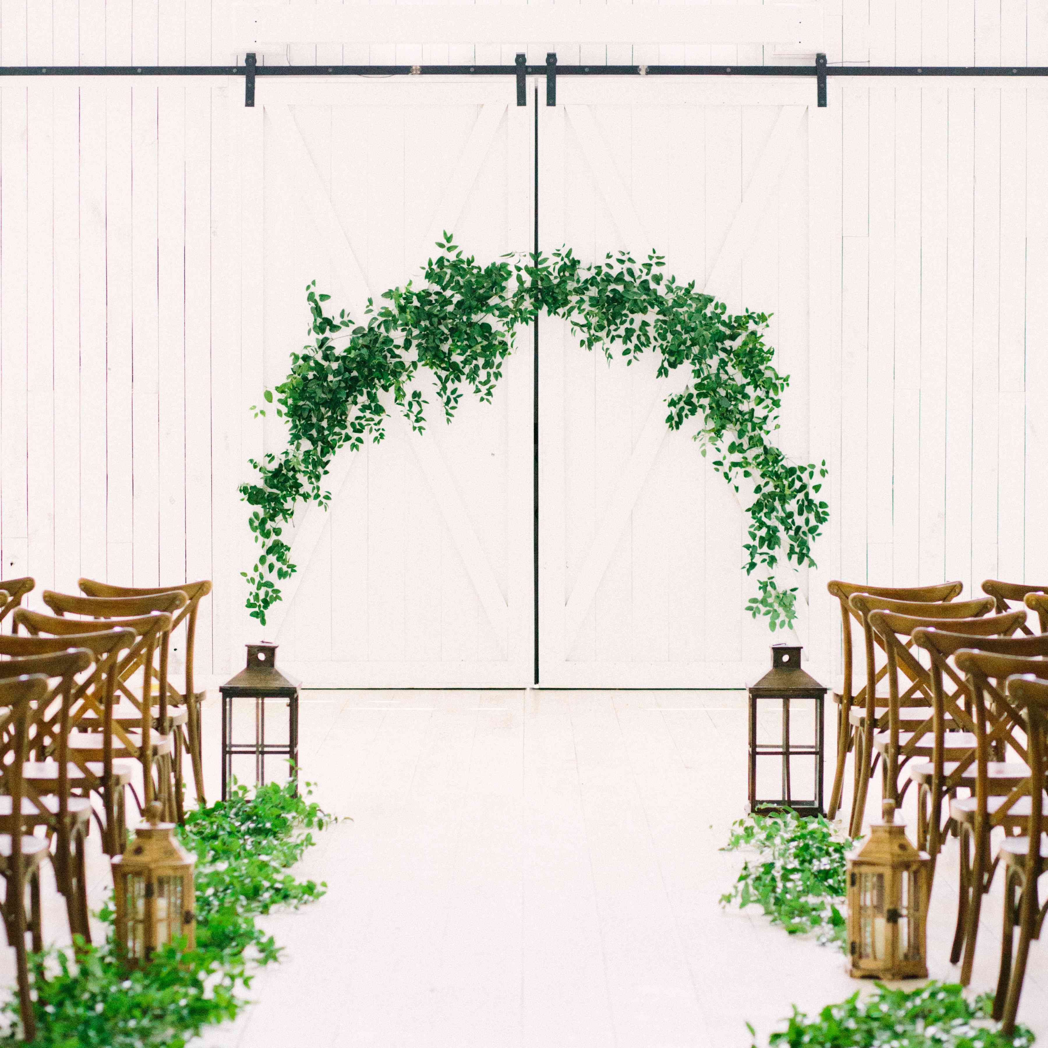 Wedding aisle with greenery and lanterns on each side of the floor and greenery arch at the end
