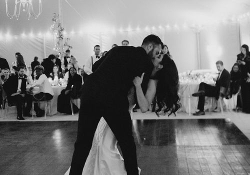 Black and white photo of could during first dance, groom dips bride and kisses her