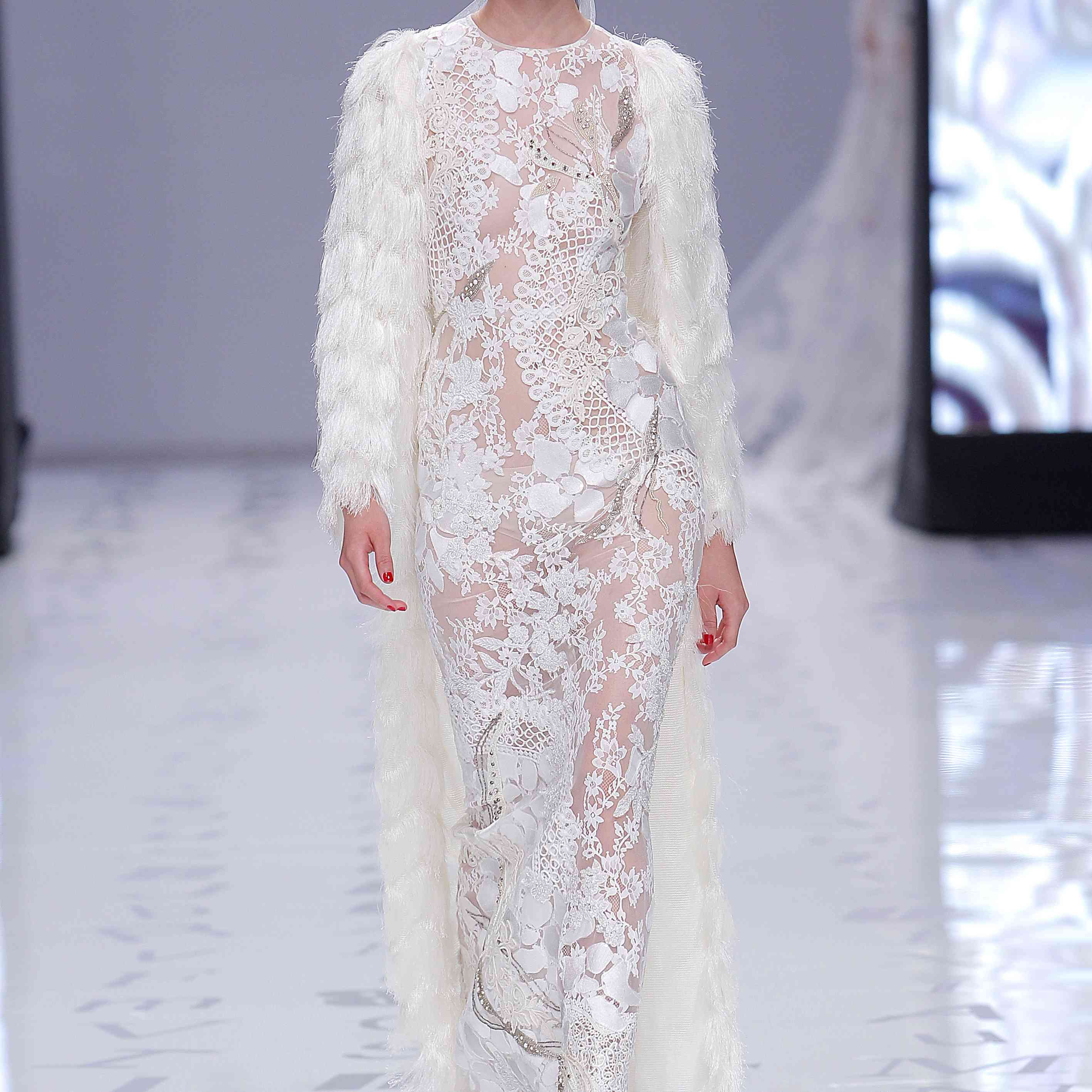 Model in an embroidered tulle mermaid dress with rhinestone appliques of different motifs and a long fringe coat