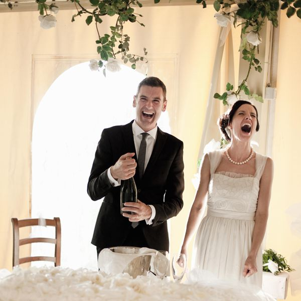 Newly married couple popping champagne