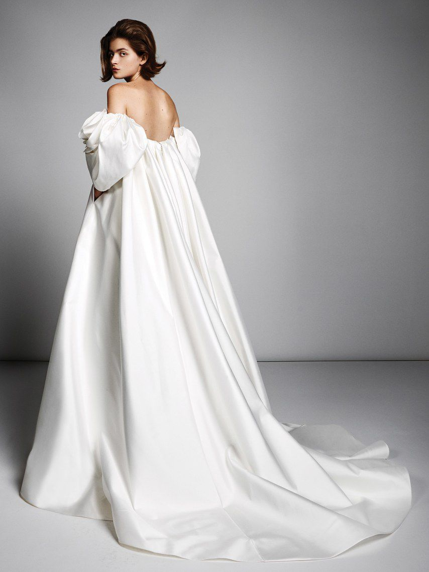 Model in white wedding gown with off-the-shoulder puffy sleeves