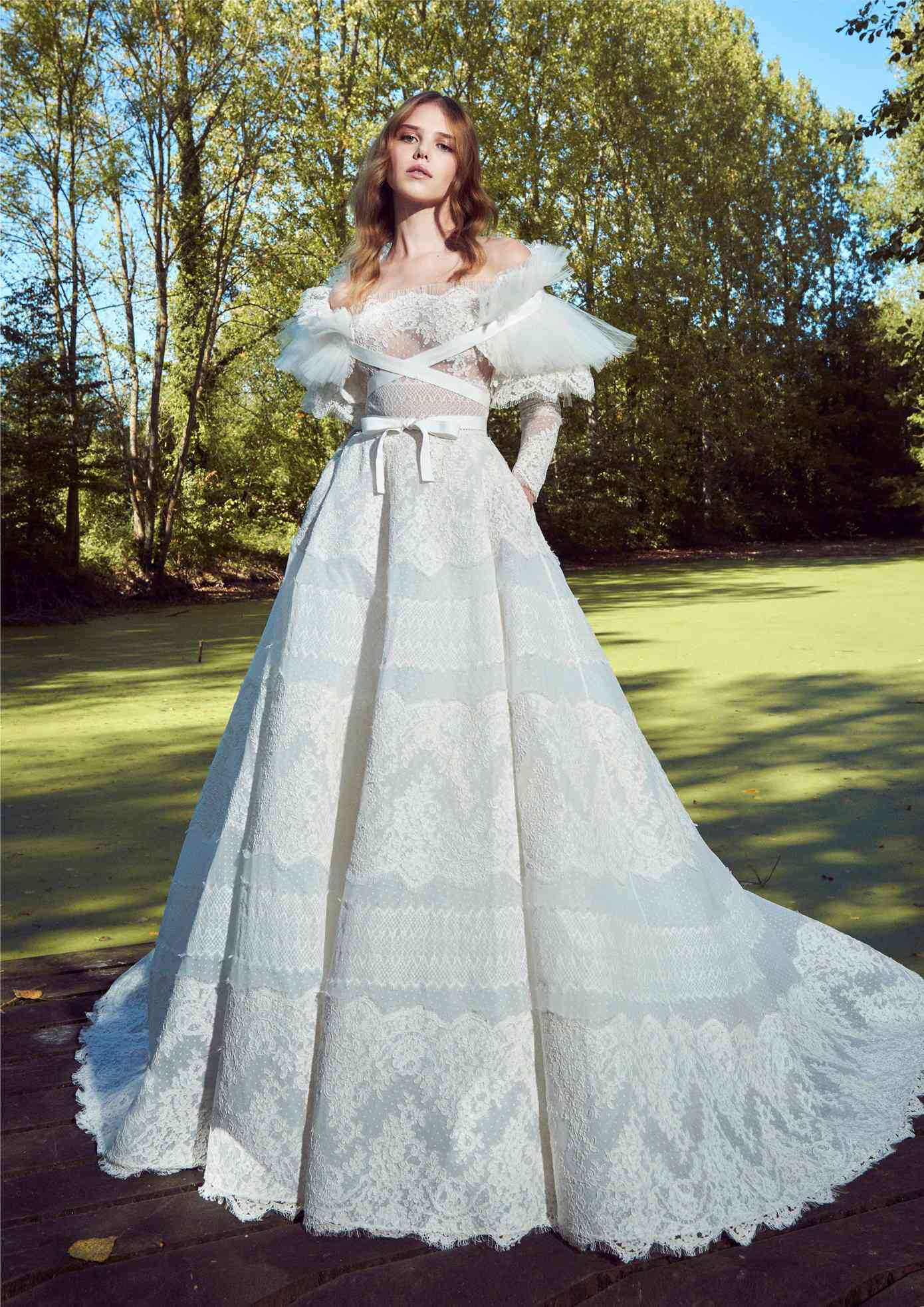 Model in off-the-shoulder long-sleeve dotted tulle ballgown with lace embroidery with a pleated tulle and lace overcoat with criss-cross ribbon