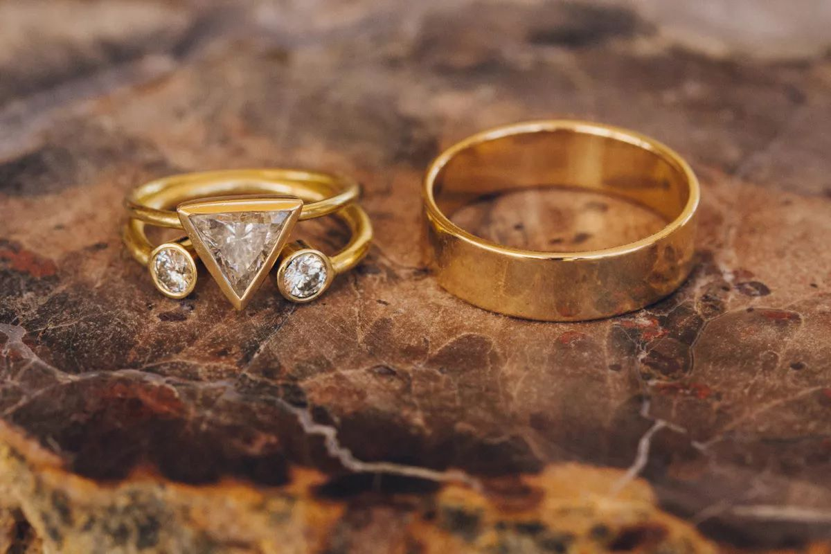 Trillion-cut diamond engagement ring with two round diamond accents on gold band