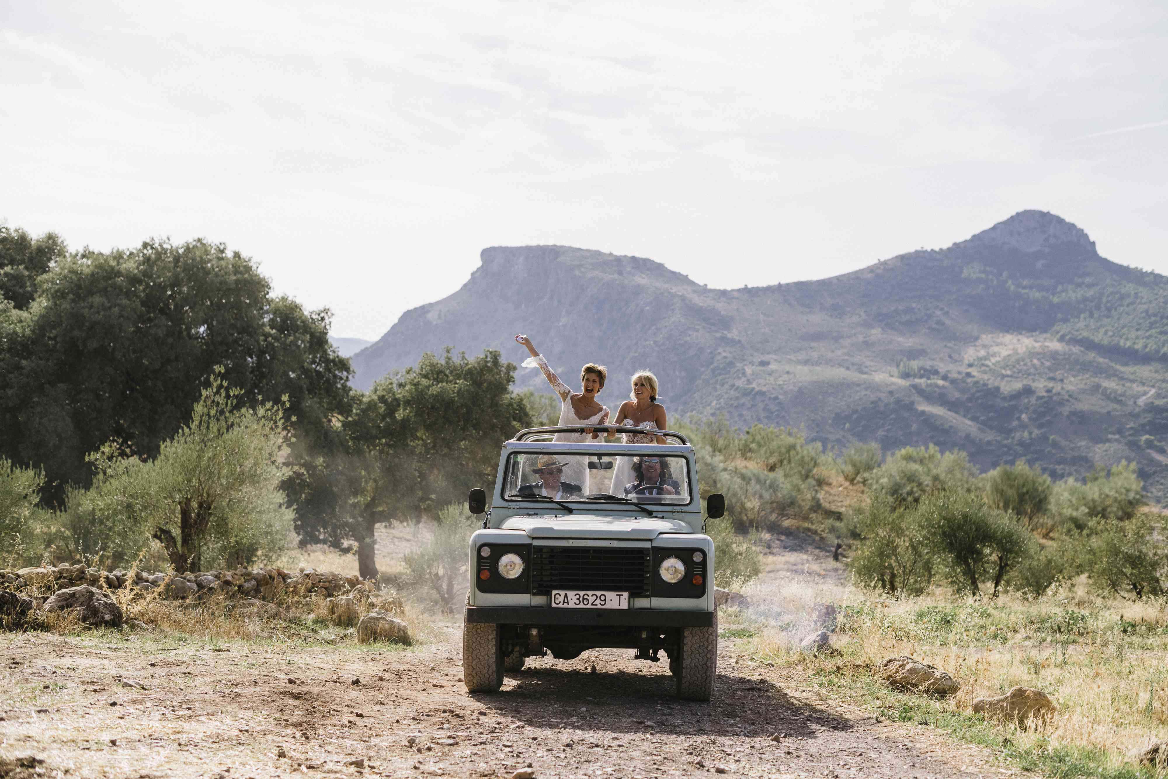 Brides arriving at ceremony in land rover