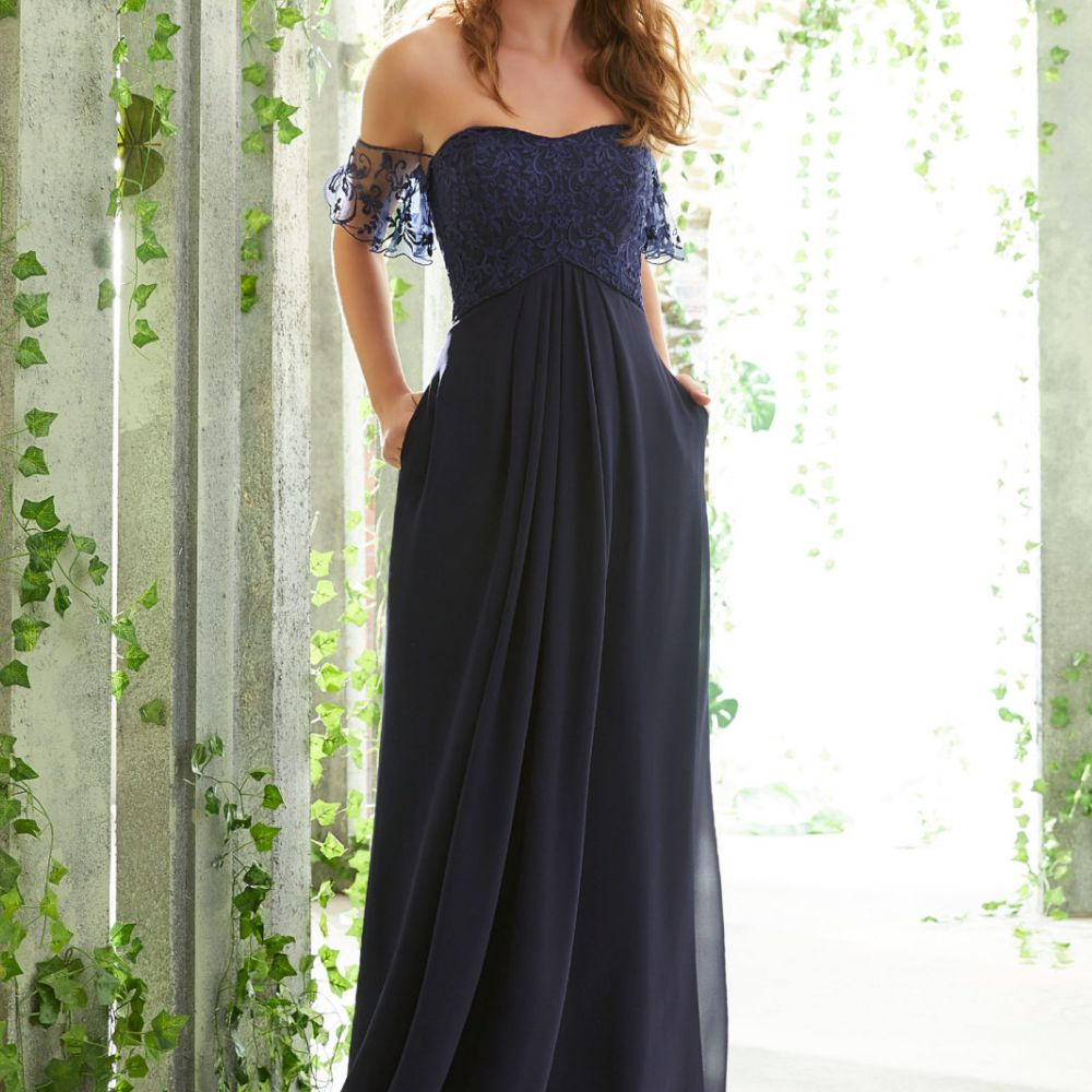 Model in off-the-shoulder dark blue gown with lace sleeves and bodice