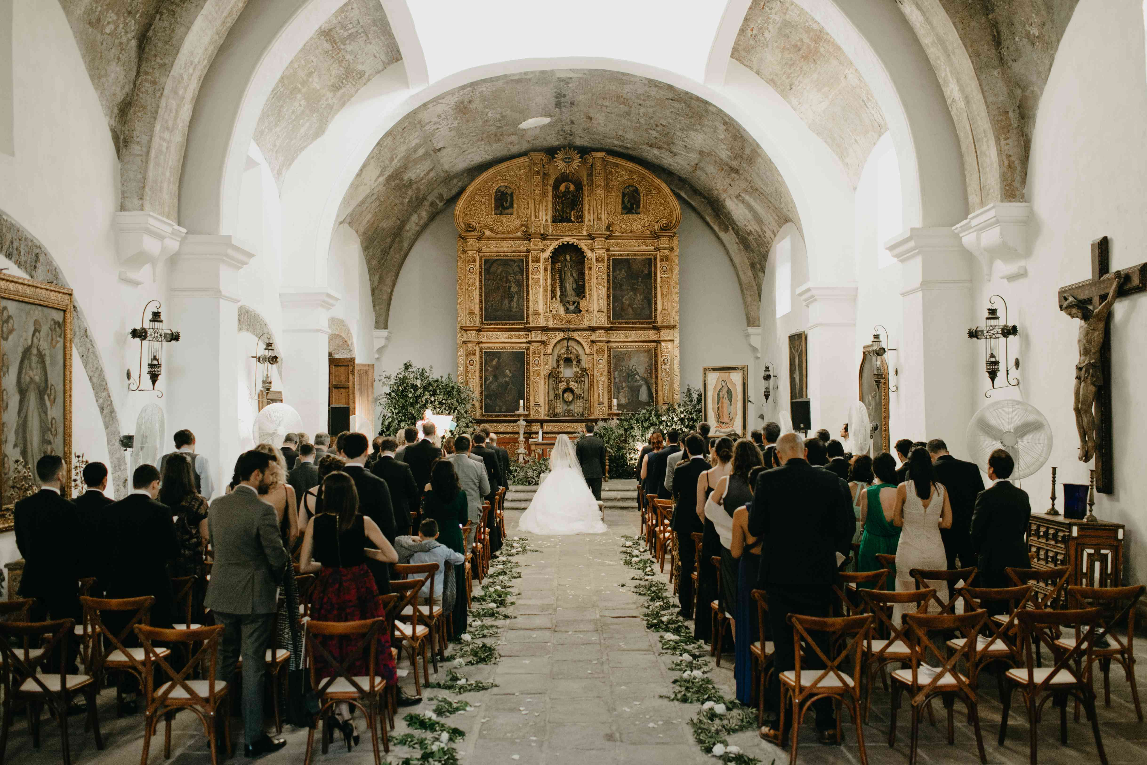 Wedding aisle with bride, groom, and guests facing front of church