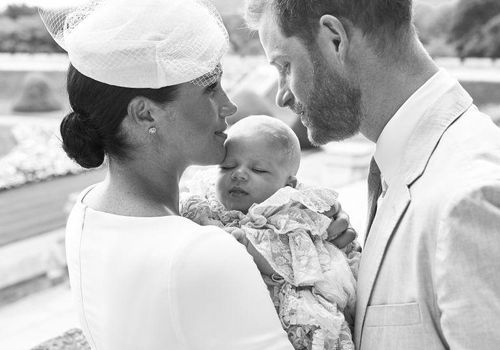 Prince Harry and his wife Meghan hold their baby son, Archie Harrison Mountbatten-Windsor at Windsor Castle with the Rose Garden in the background, west of London on July 6, 2019.