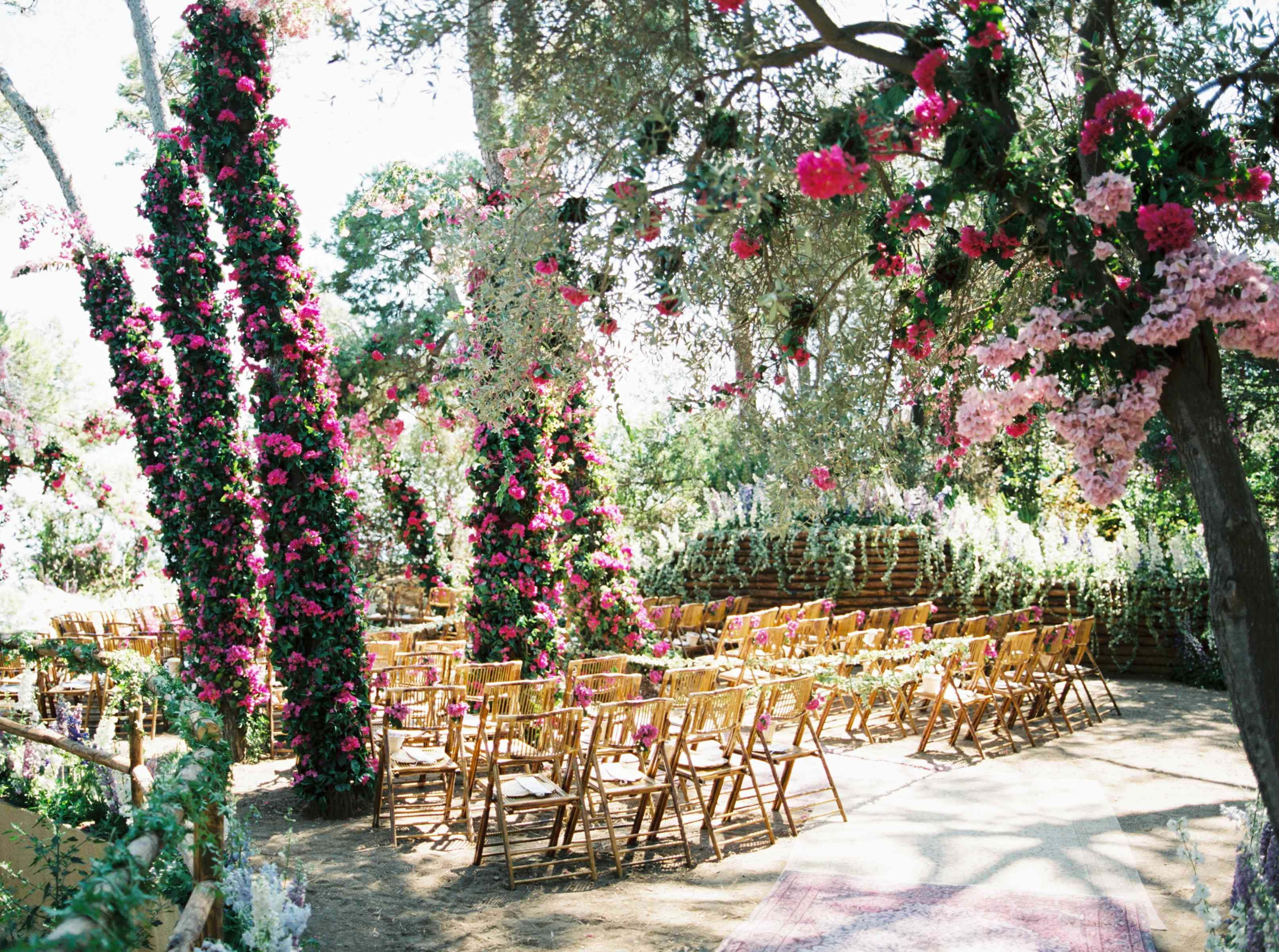 Ceremony site with tall rose bushes lining the aisle