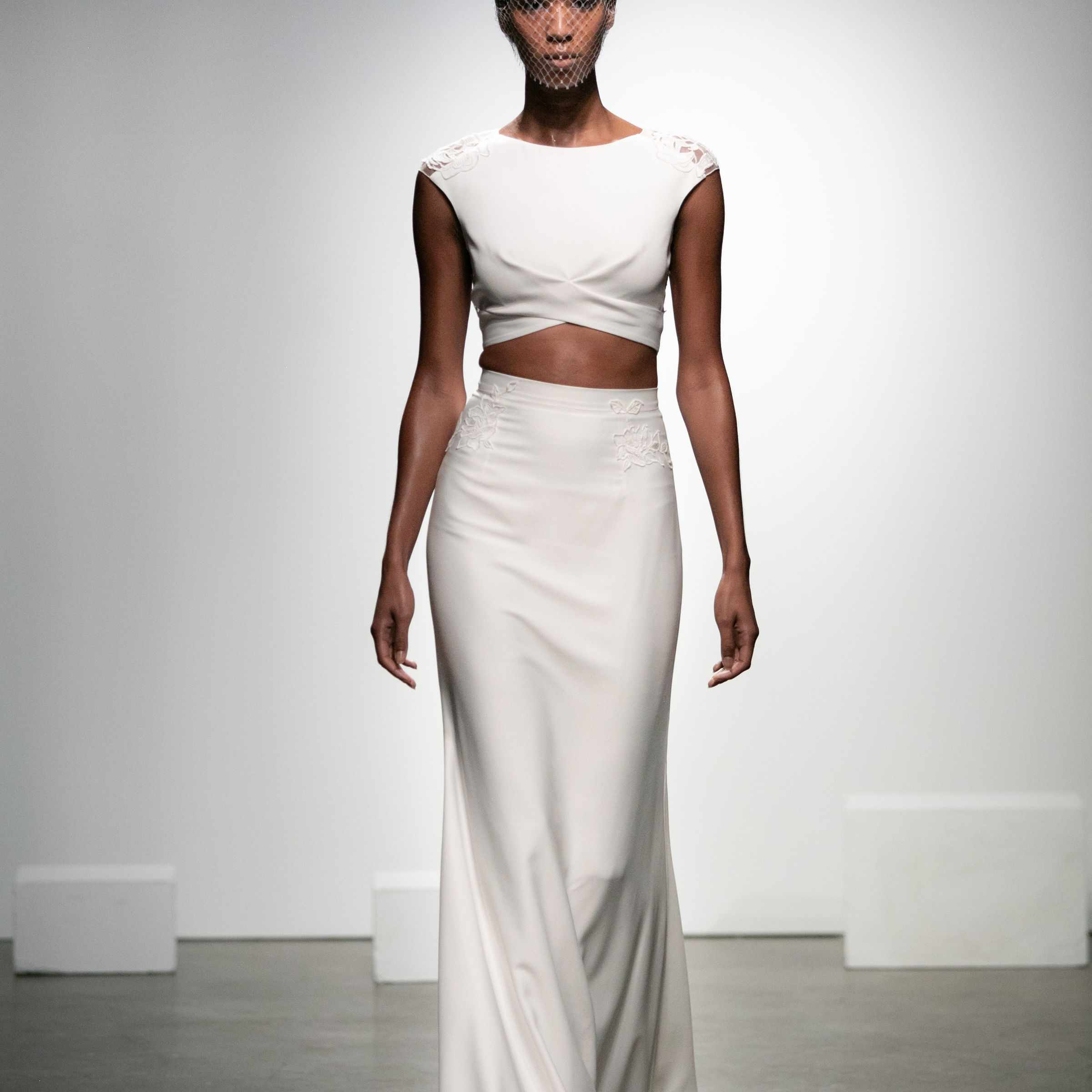 Model in crop top and skirt ensemble in crepe with appliquéd graphic rose patterned lace