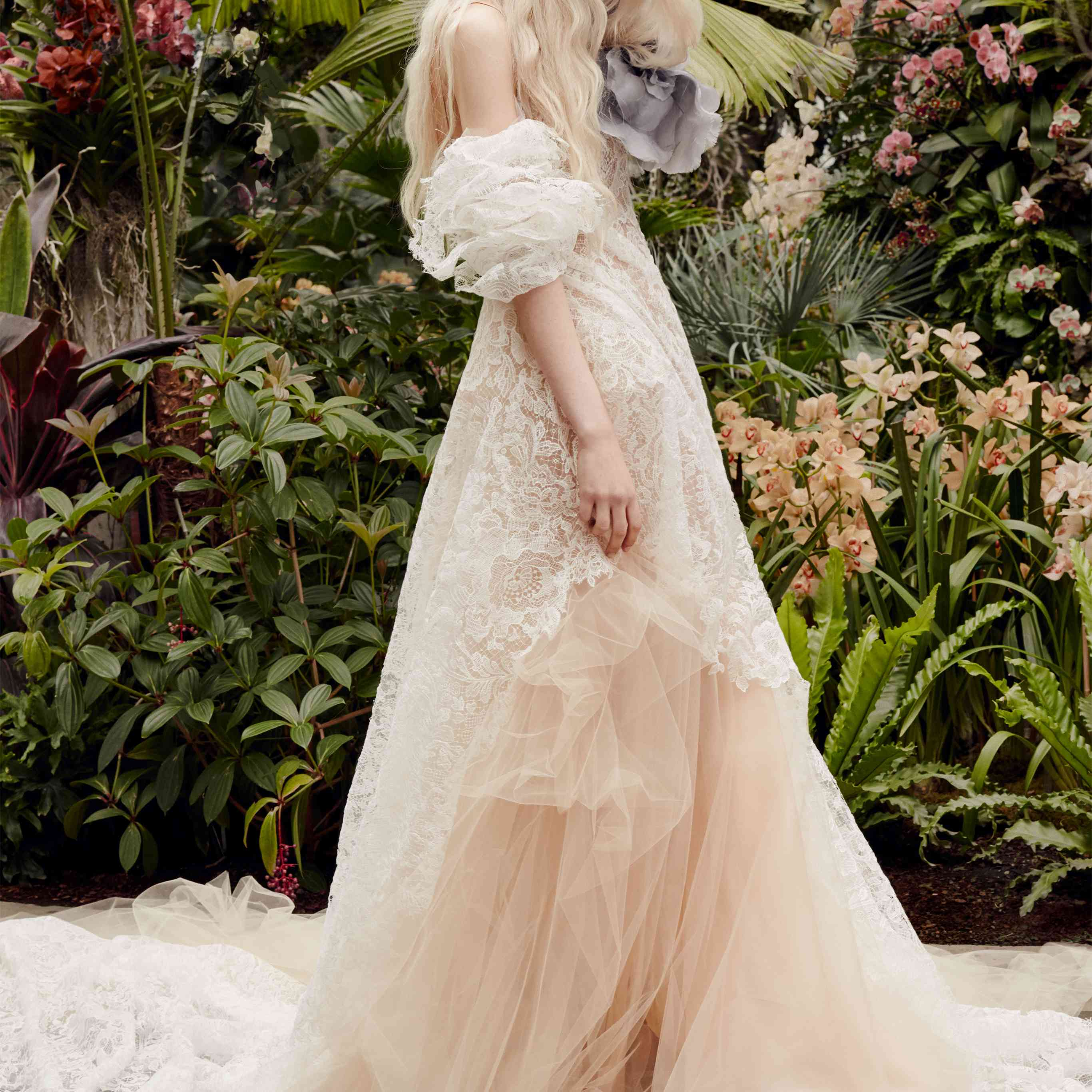 Model in white lace and nude tulle off-the-shoulder gown with dramatic puff sleeves