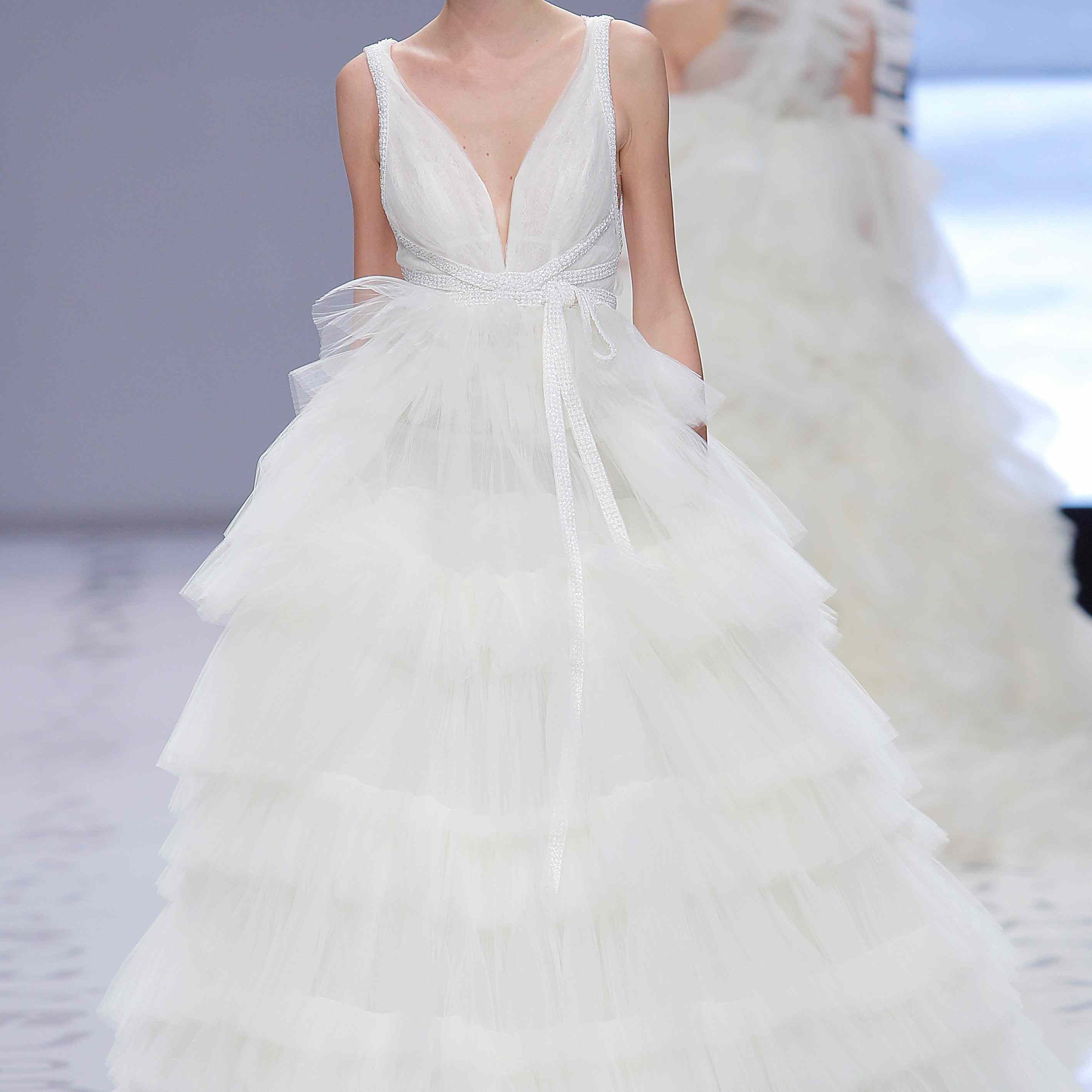 Model in a pleated tulle princess dress with a voluminous ruffle skirt, rhinestone belt, and deep V-neck bodice