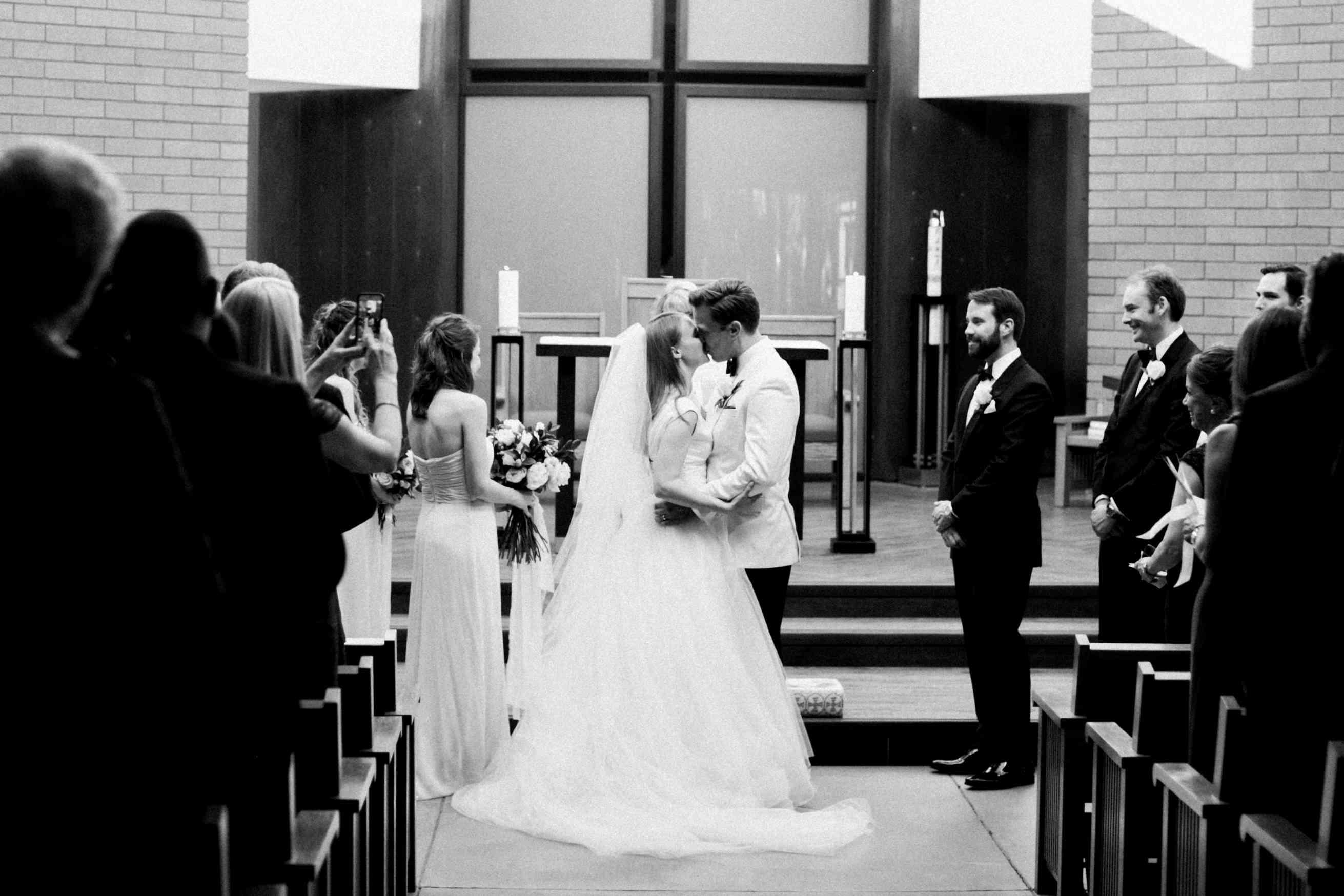 Bride and groom kiss at altar