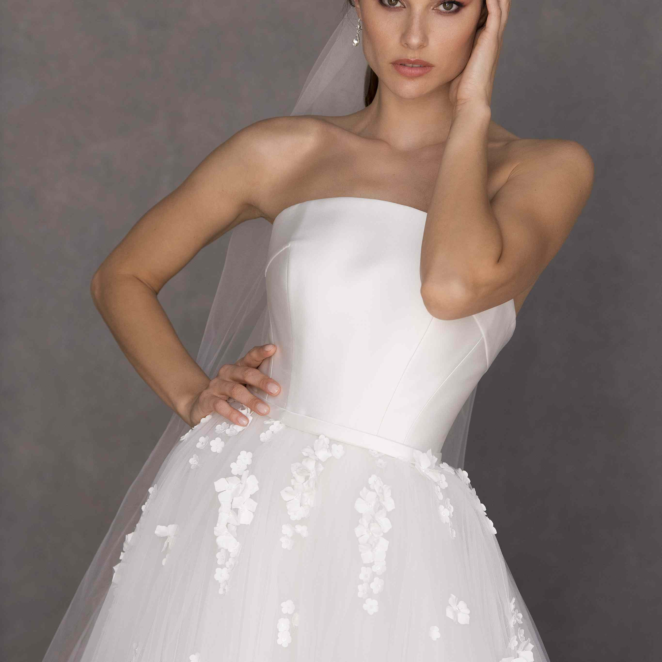 Model in strapless ballgown with a silk bodice and tulle skirt with floral appliques with a matching headpiece