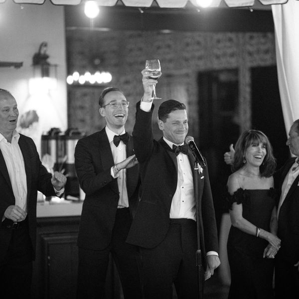 Man holding up a glass while making a wedding toast