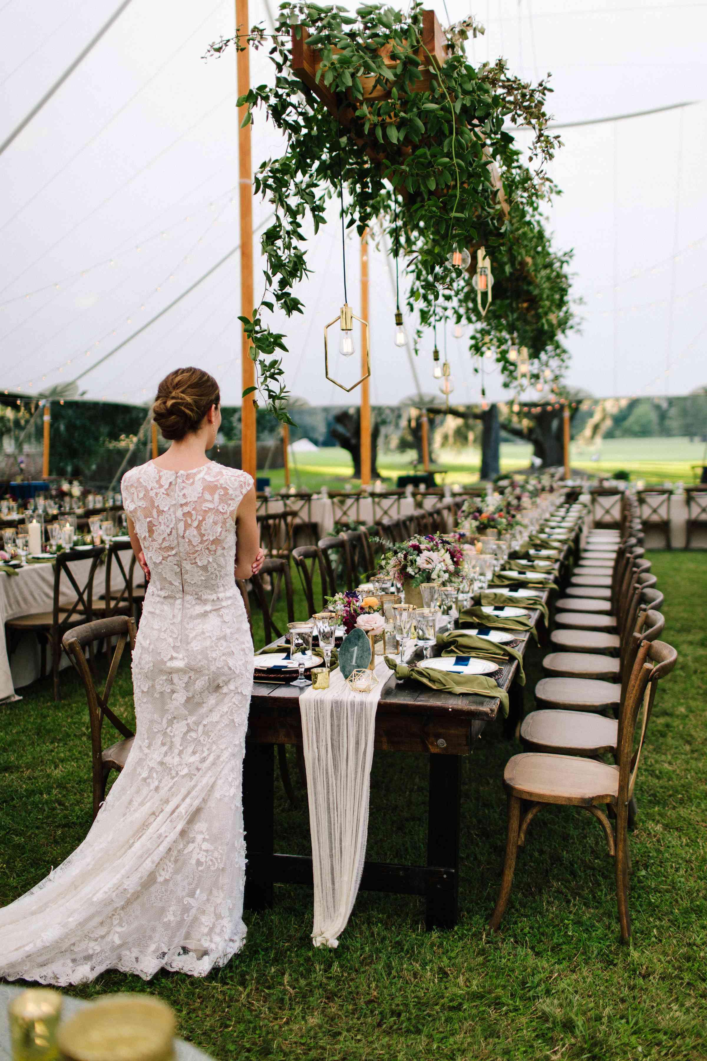 <p>Bride looking at wedding reception table</p><br><br>