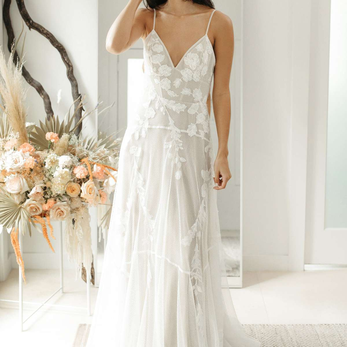 Model in strappy V-neck net gown with flower and butterfly embroidery