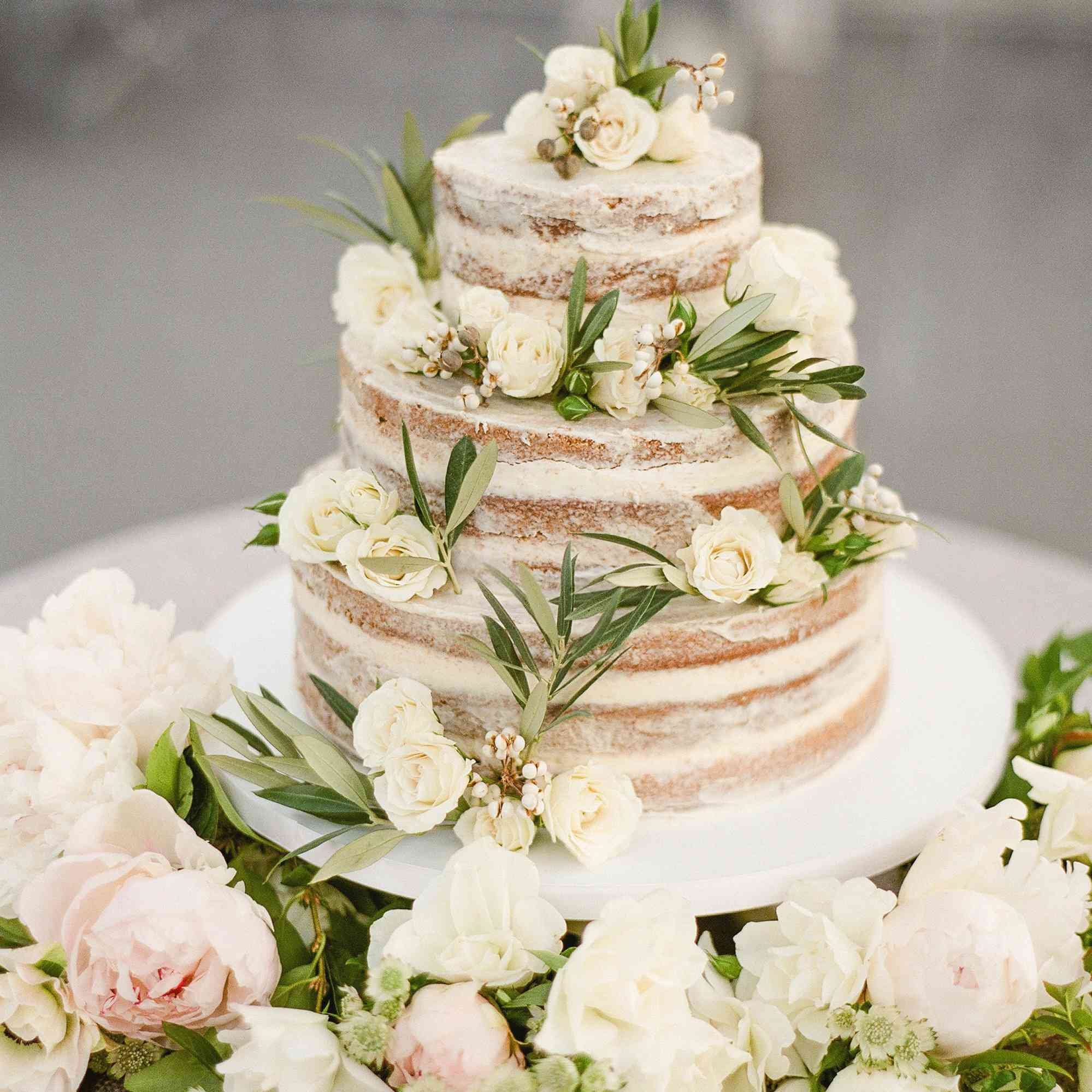 three-tier naked wedding cake with fresh flowers