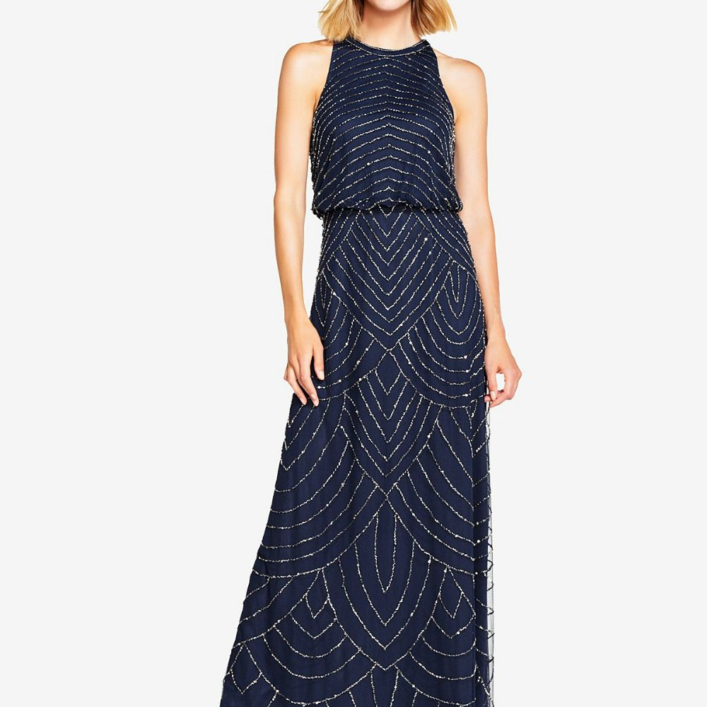 Woman in a high-neck sleeveless navy blue dress with a shimmery art-deco pattern