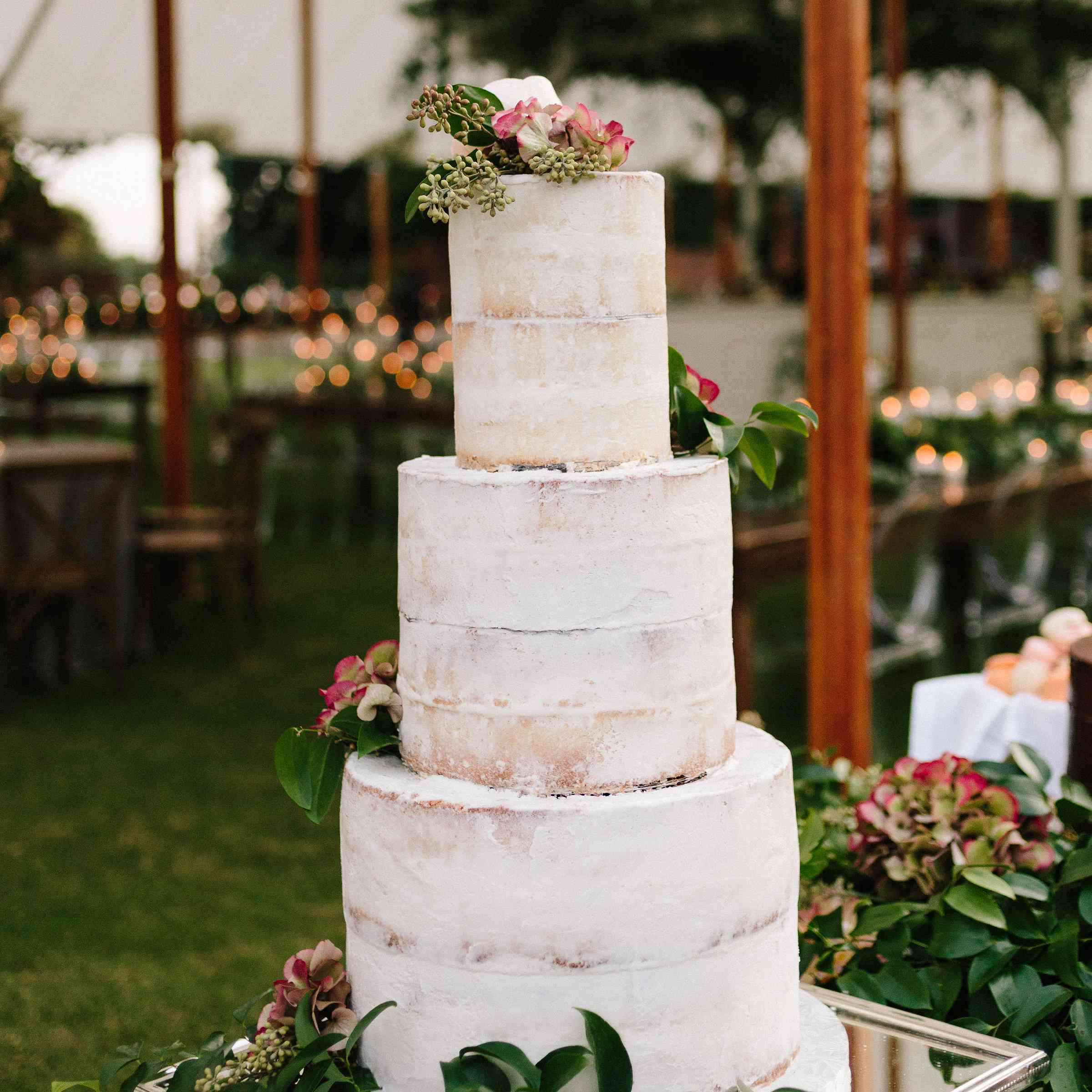 Elongated tiered semi-naked wedding cake with floral accents and strawberry filling