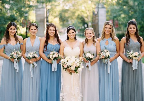 A bride surrounded by her bridesmaids, who are wearing dresses in different shades of blue
