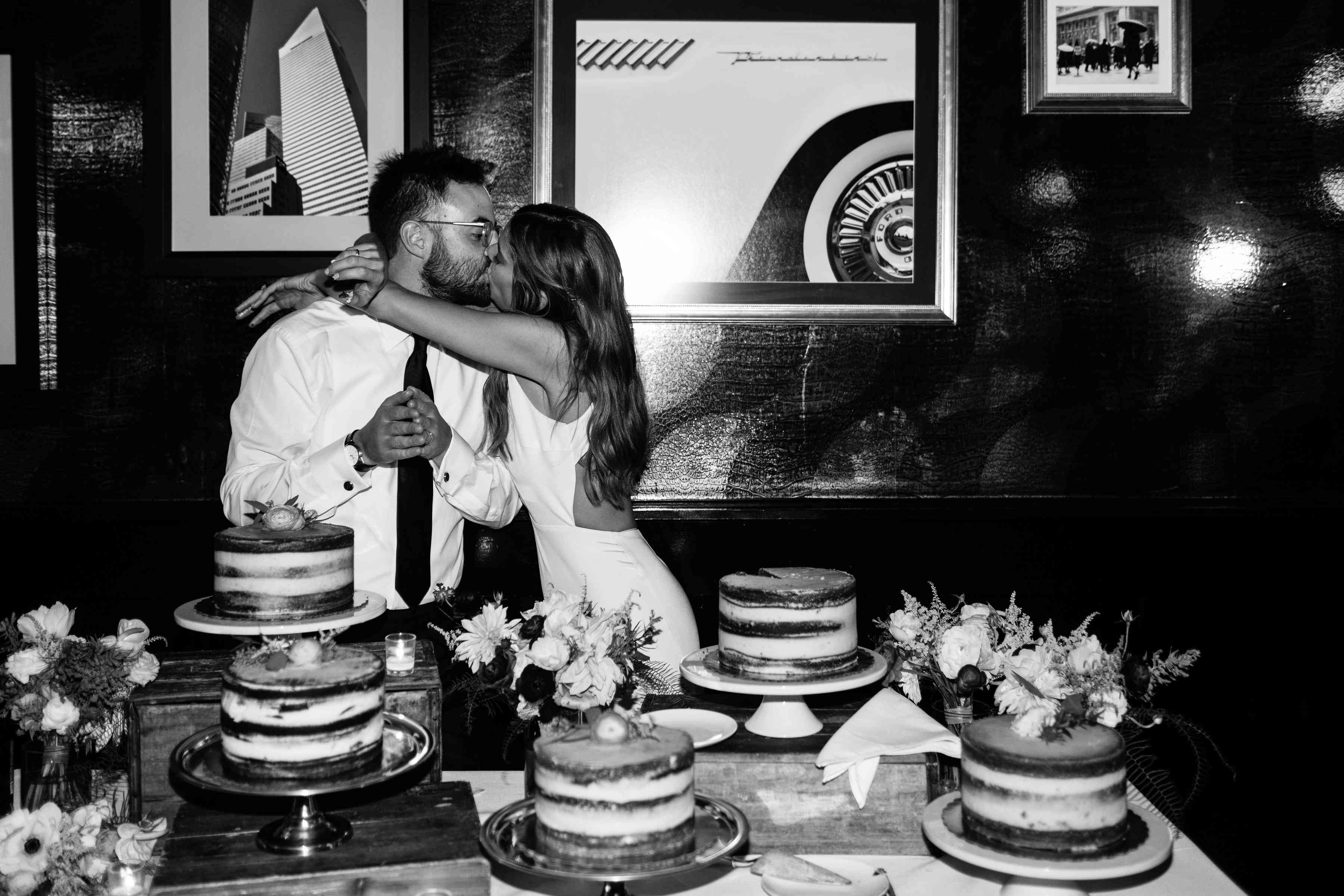 Bride and groom kissing near cakes