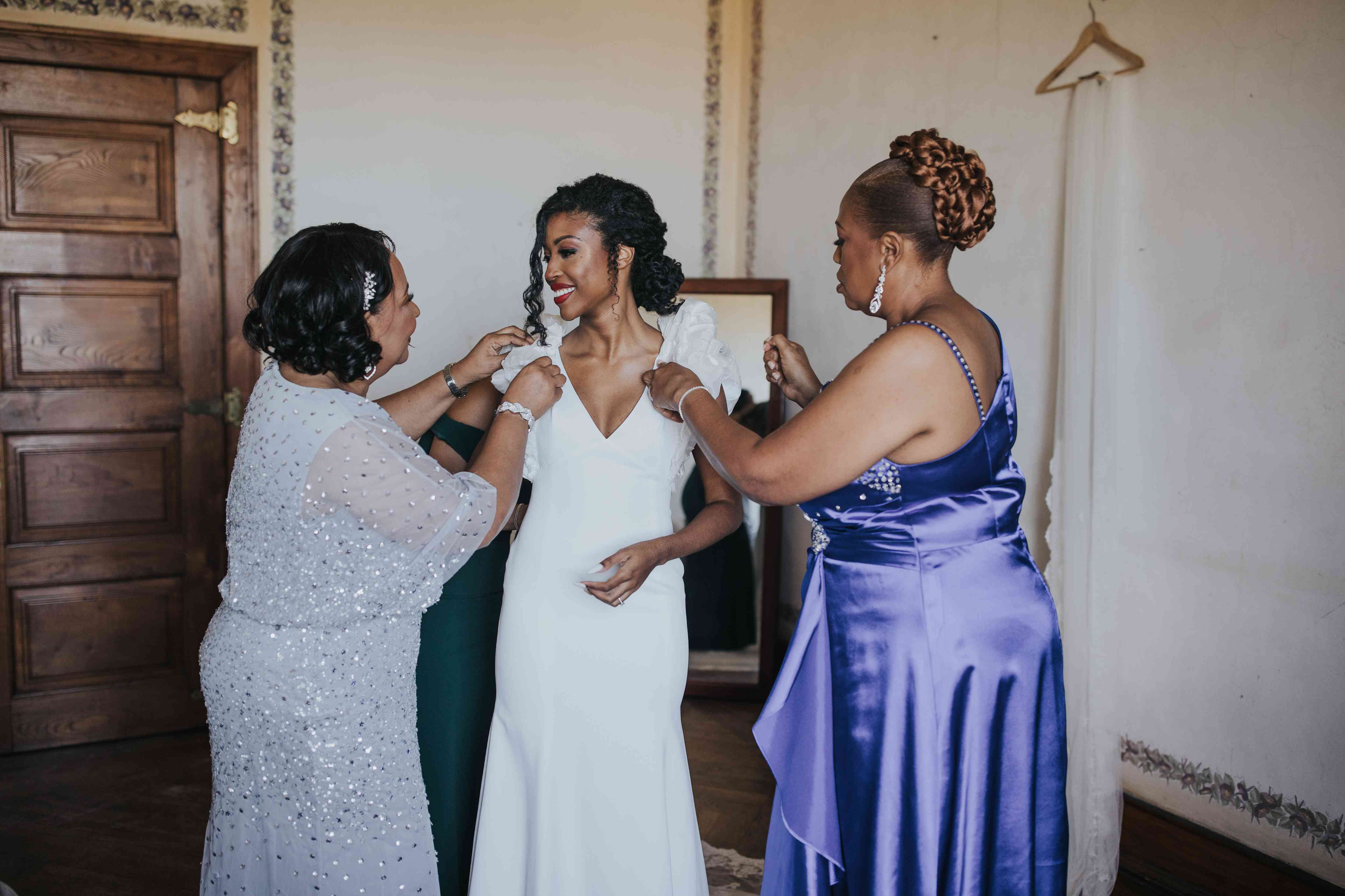 Family helping the bride put on her dress