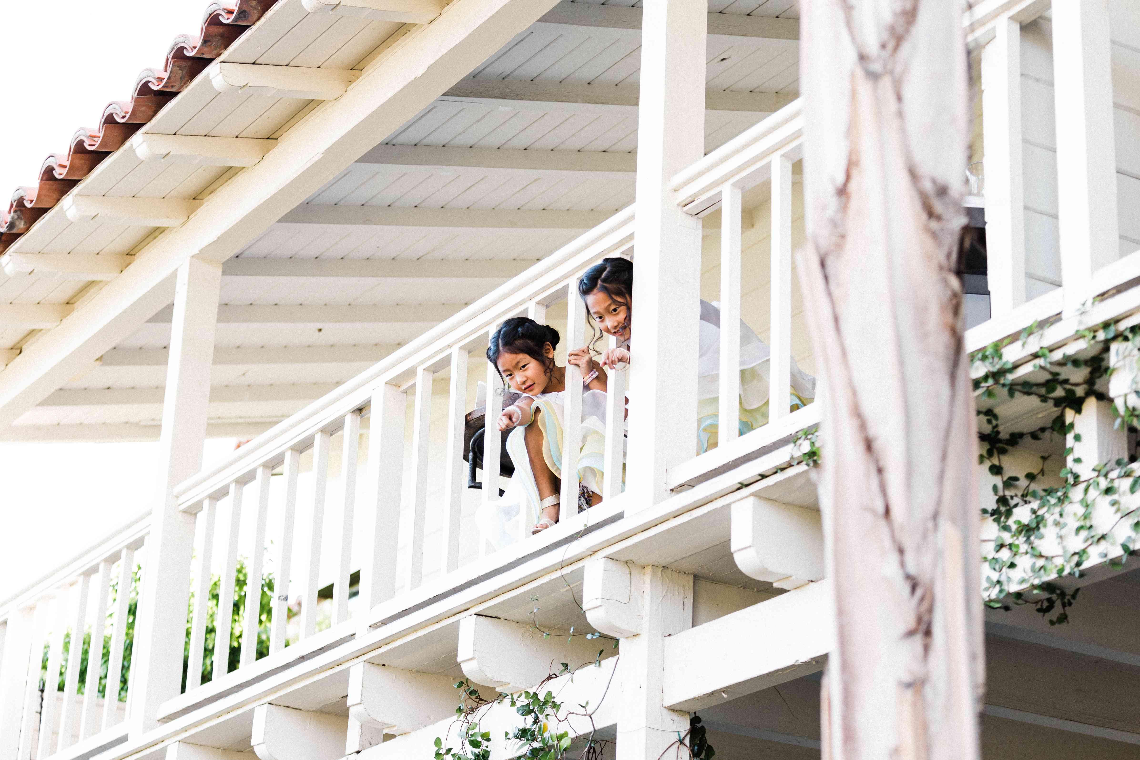 Flower girls peeking from balcony