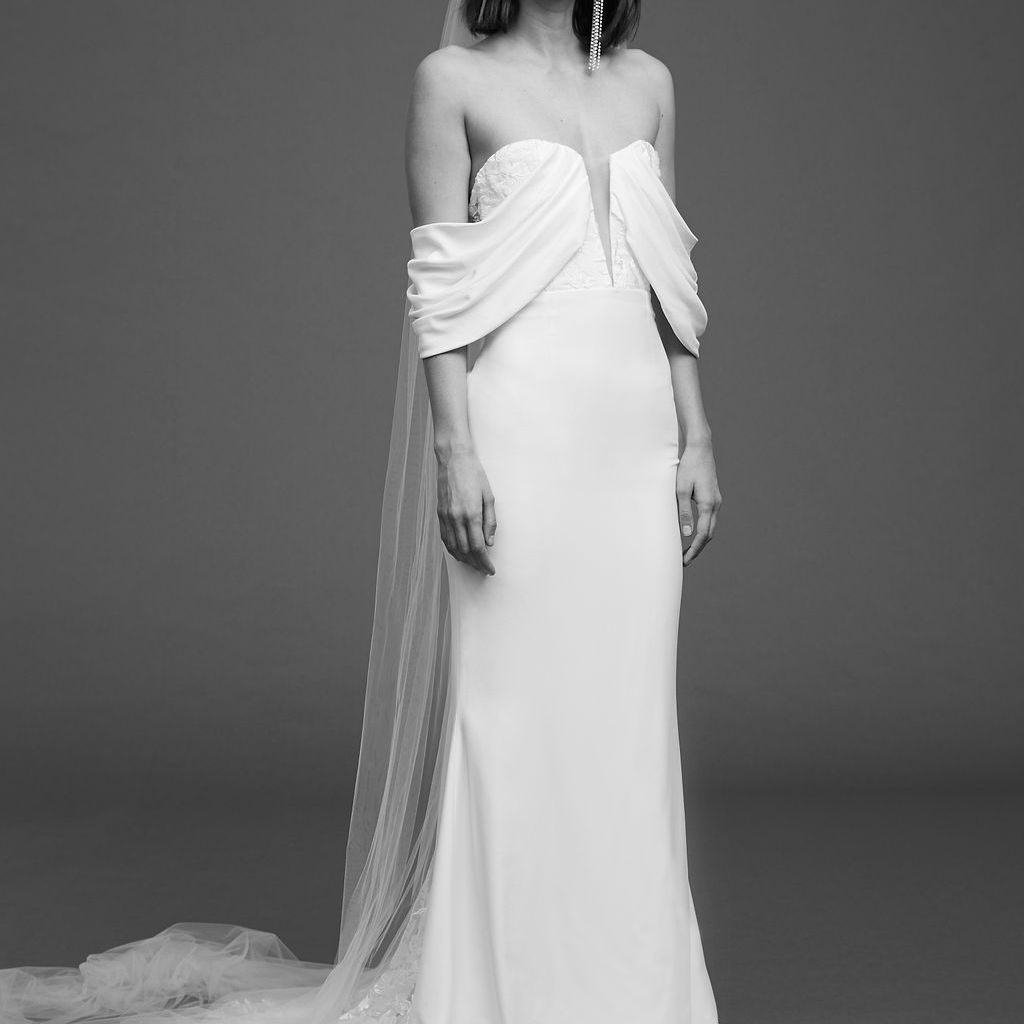 Model in off-the-shoulder dress with draped sleeves and illusion tulle neckline