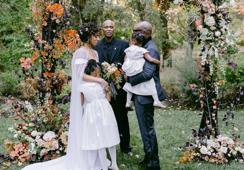 bride and groom at altar with two daughters
