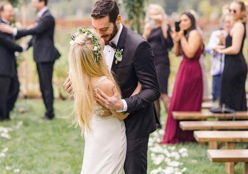 Bride wearing floral crown kissing groom