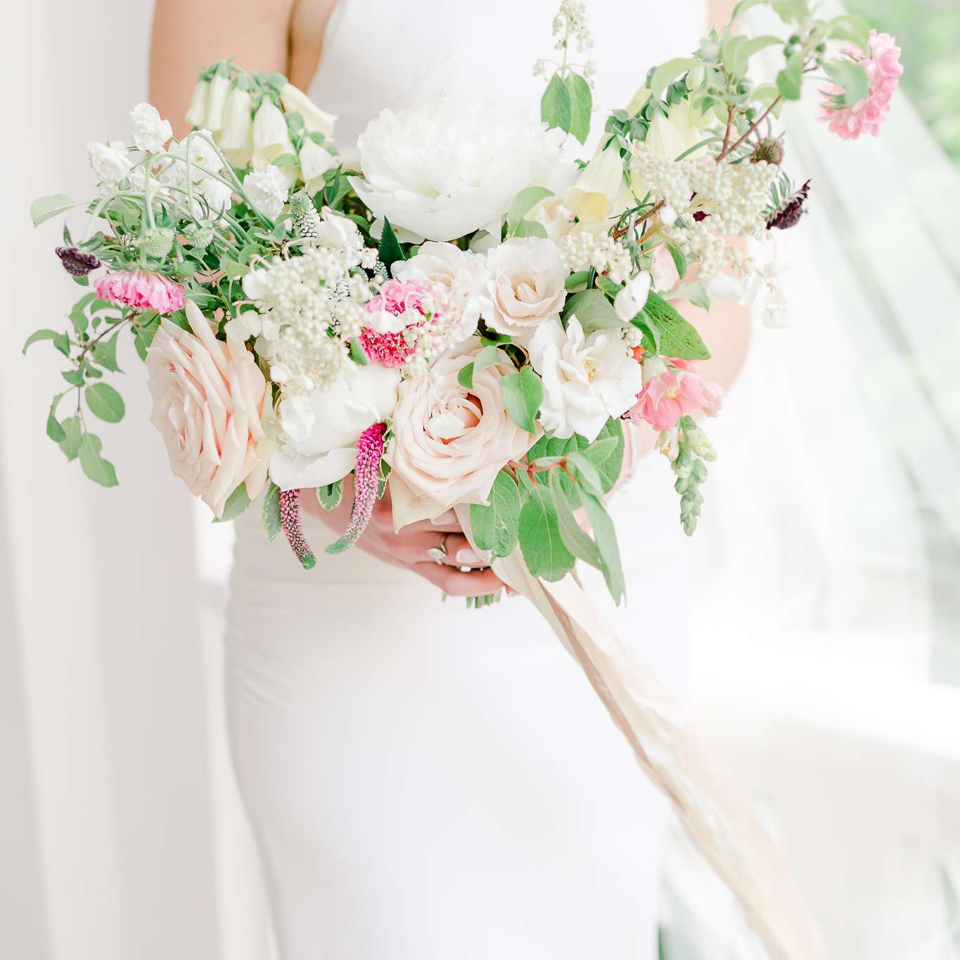 Bride holding pink and white bouquet of peonies, roses, foxgloves, hydrangea, snapdragon, veronica, and scabiosa