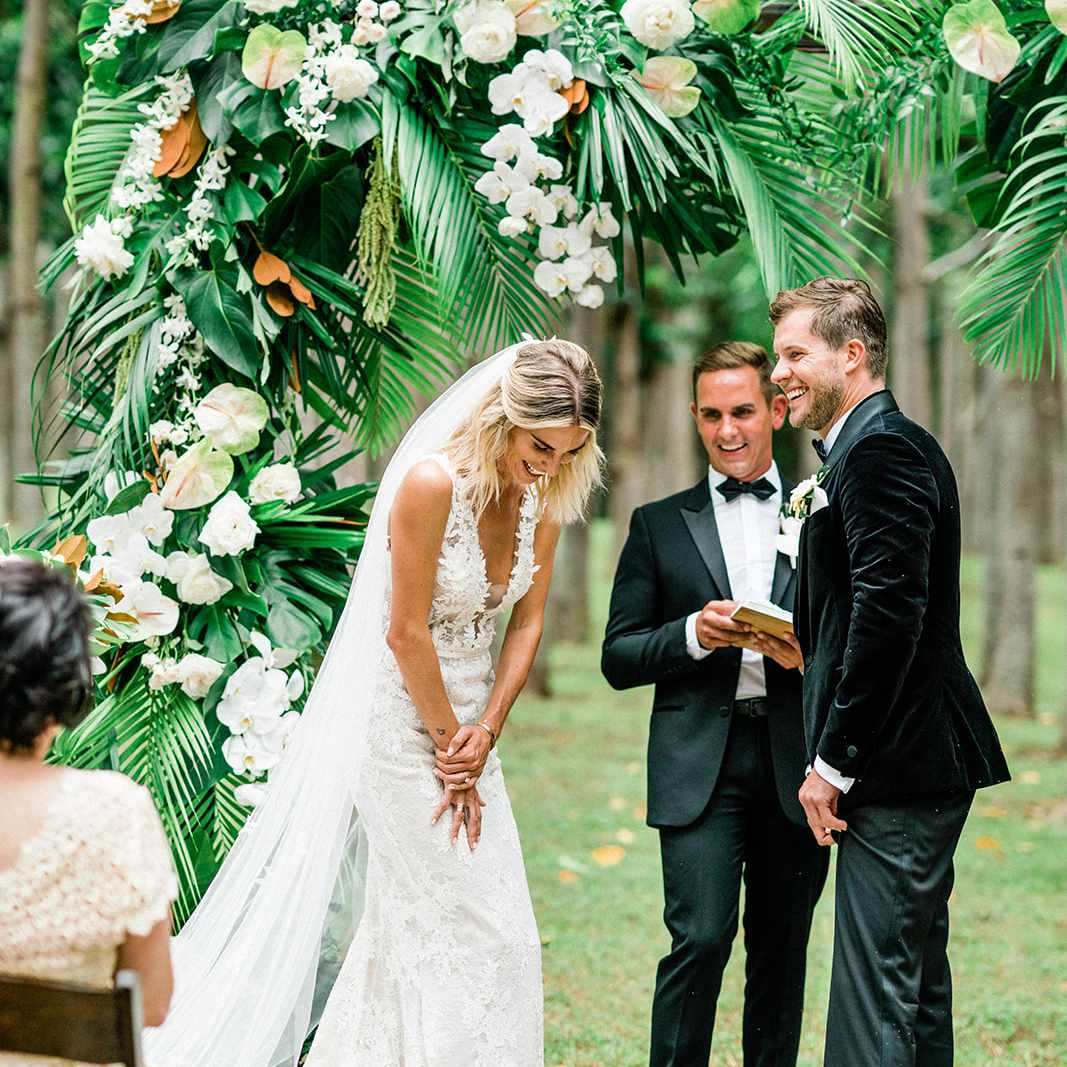 bride and groom laughing at altar