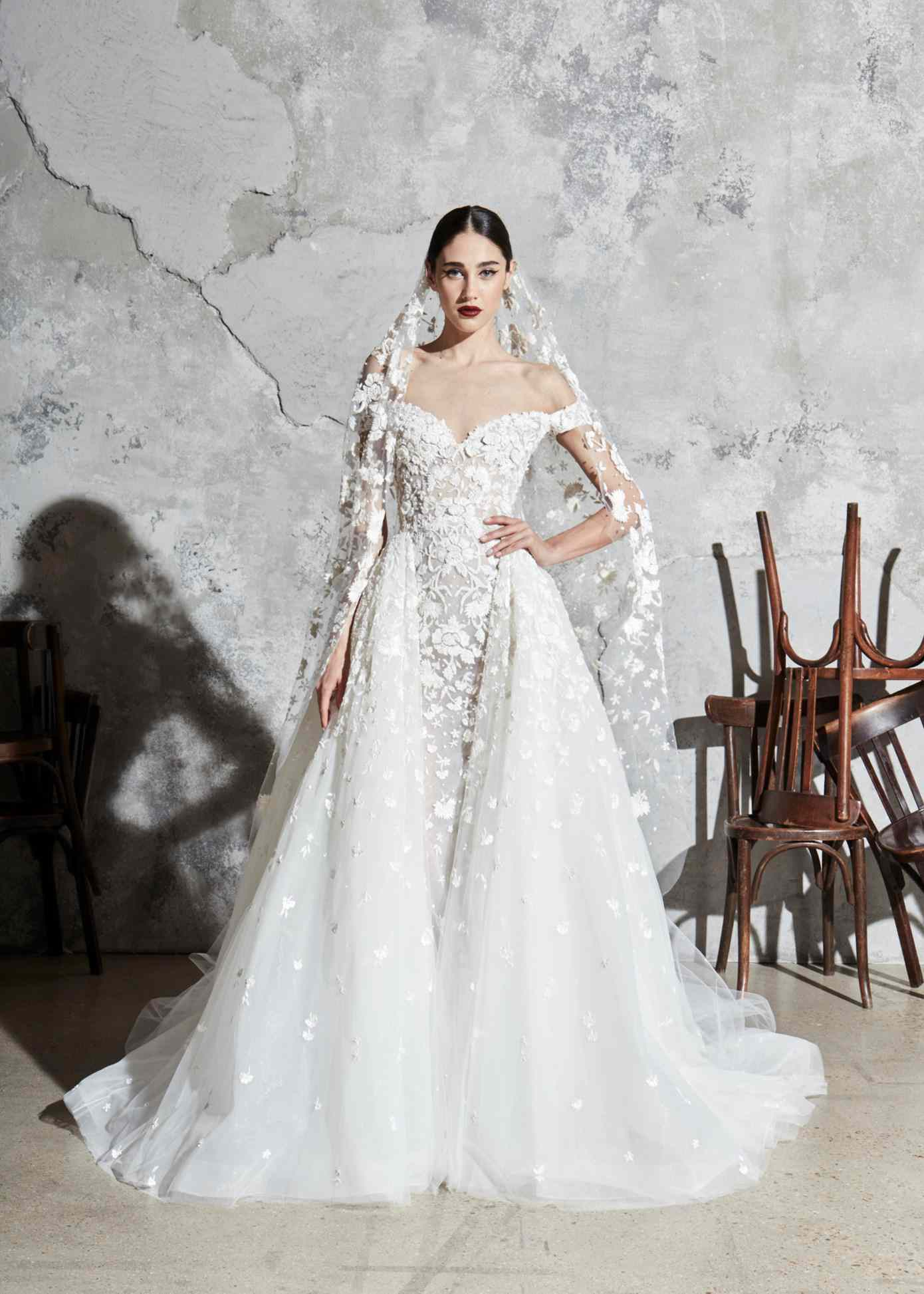 Model in off-the-shoulder tulle ballgown with a sweetheart neckline, floral embroidery and appliques with a matching veil