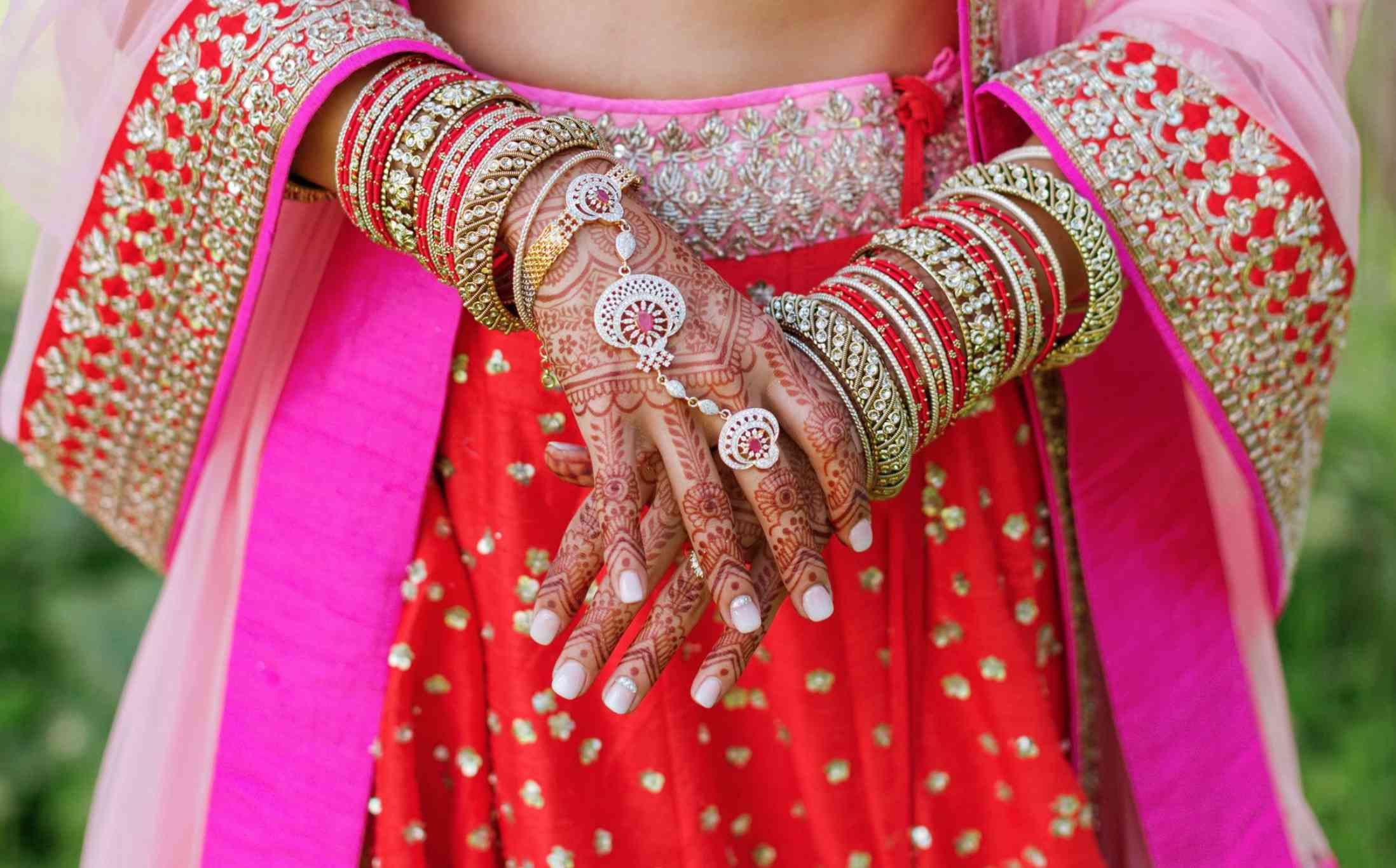Bride with henna tattooed hands with white nail polish with rhinestone embellishments