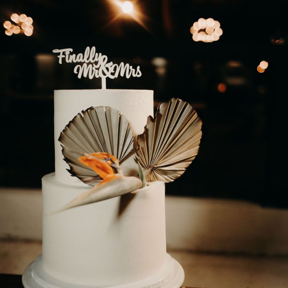 White two-tiered wedding cake with dried palm leaves