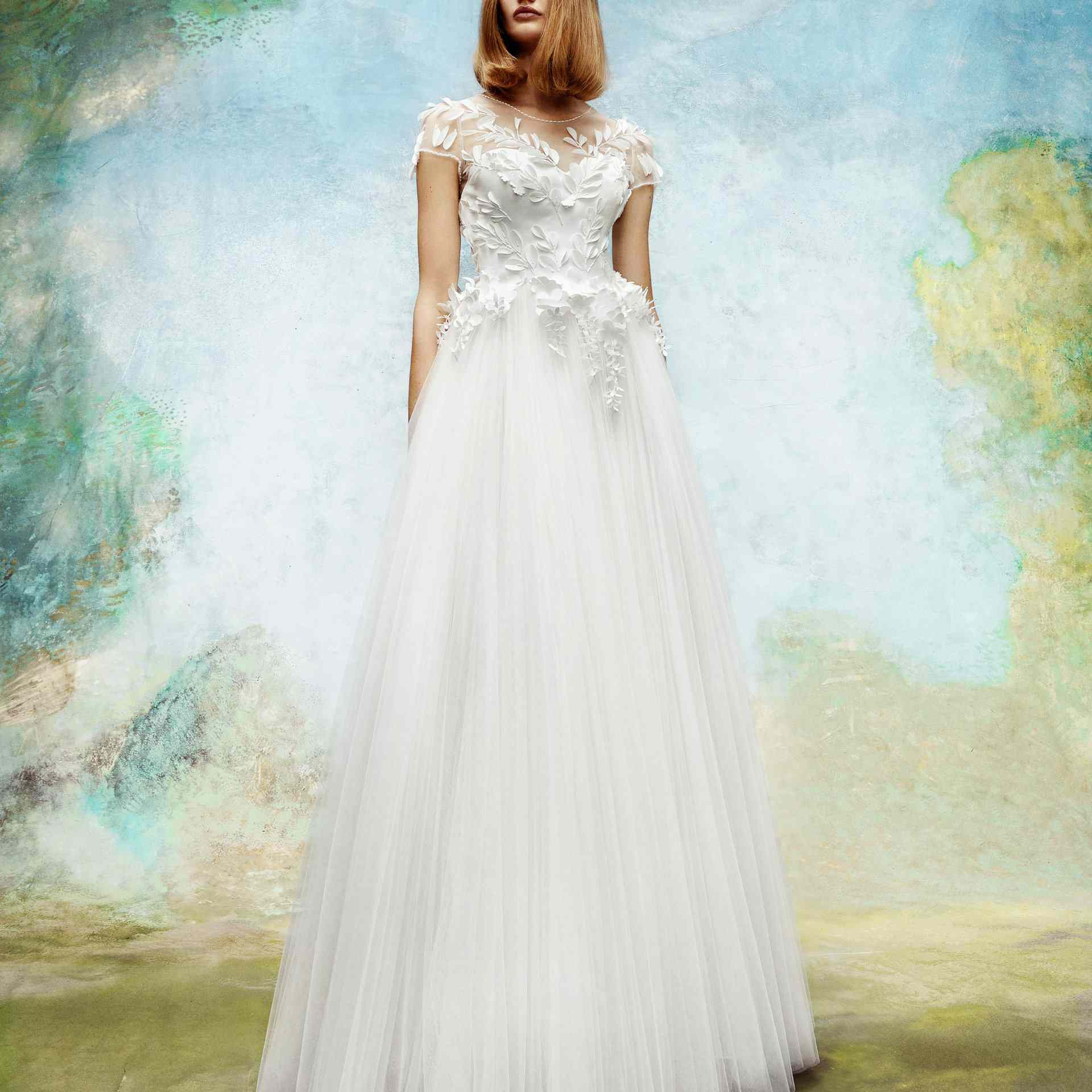 Model in wedding gown with tulle skirt and floral embellishments