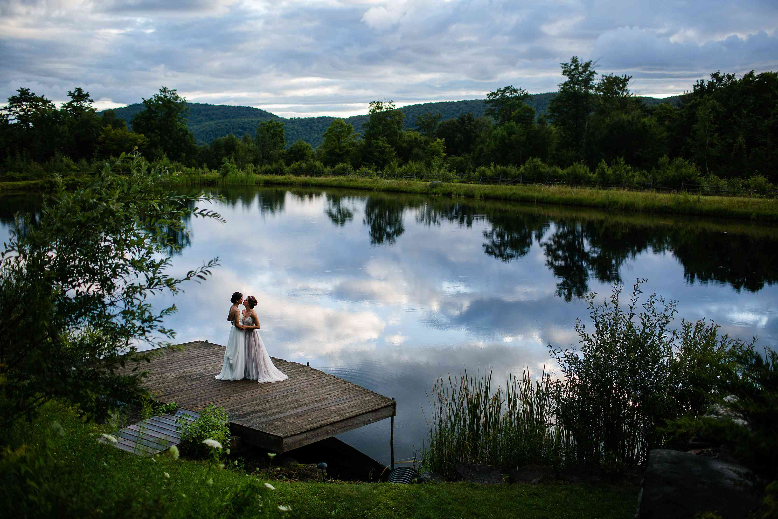 Two brides embracing by scenic lakeside.