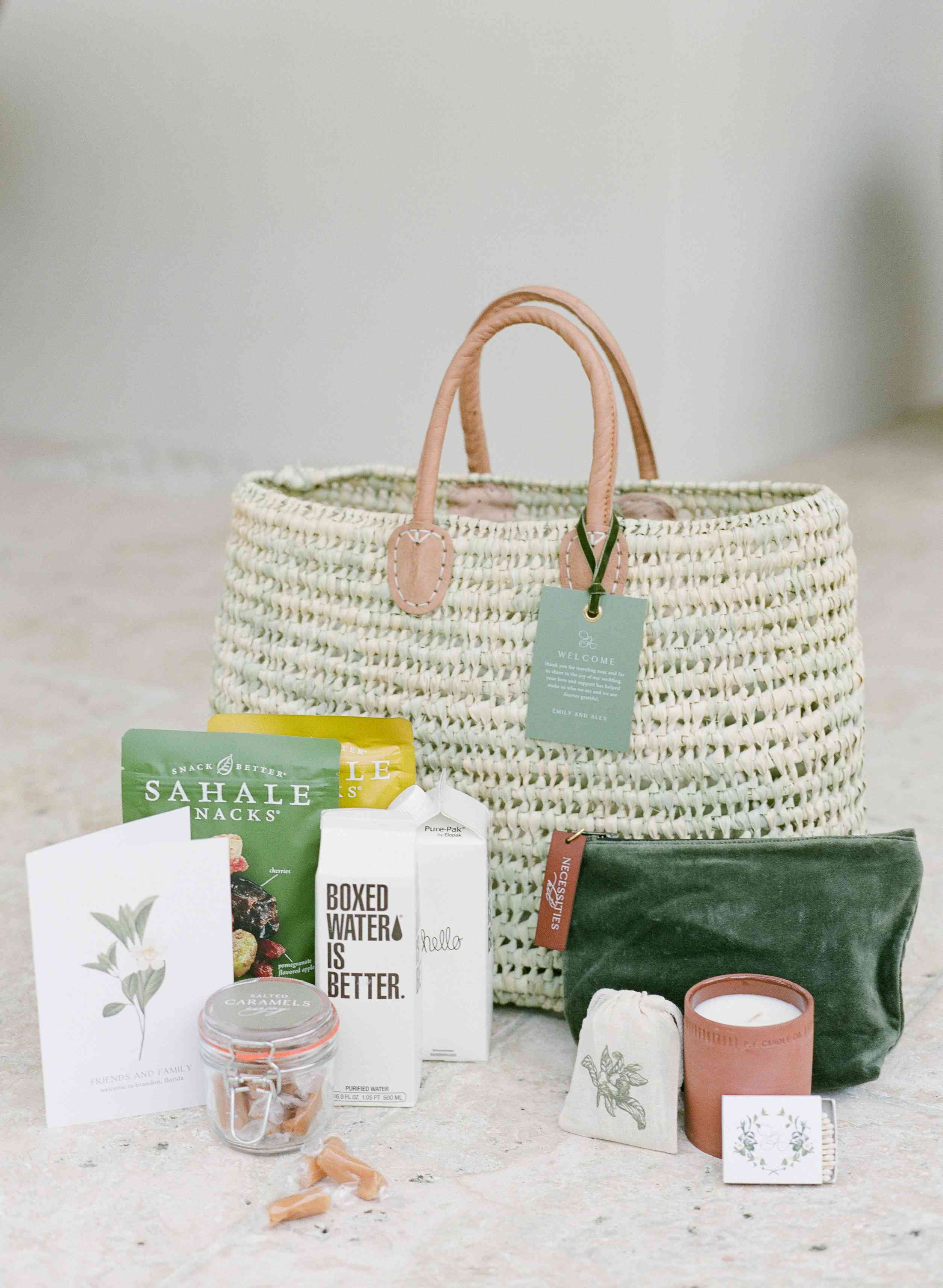 Welcome bag with boxed water, jar of caramels, candle, snacks, and reusable tote bag