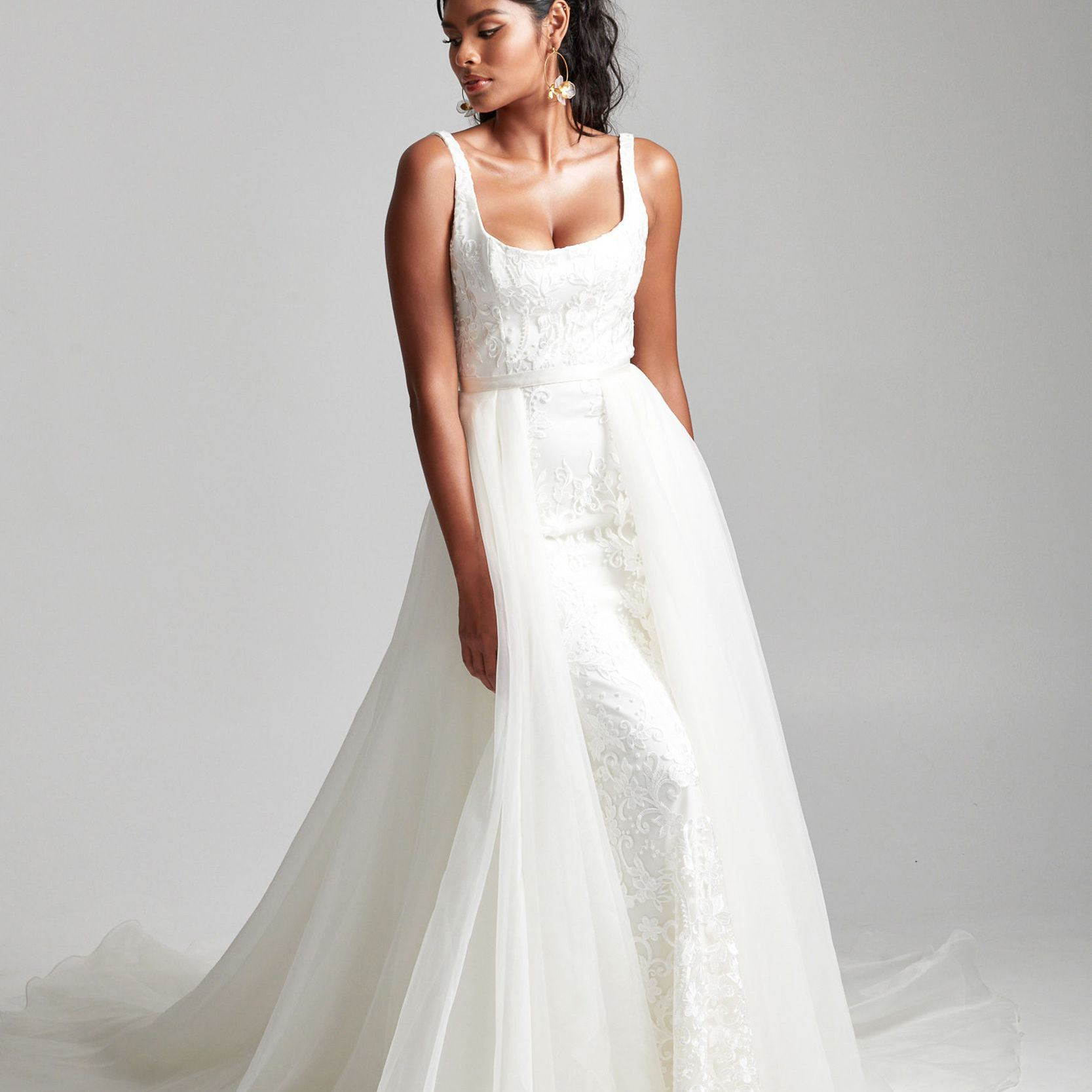 Model in sleeveless lace wedding gown with tulle overskirt