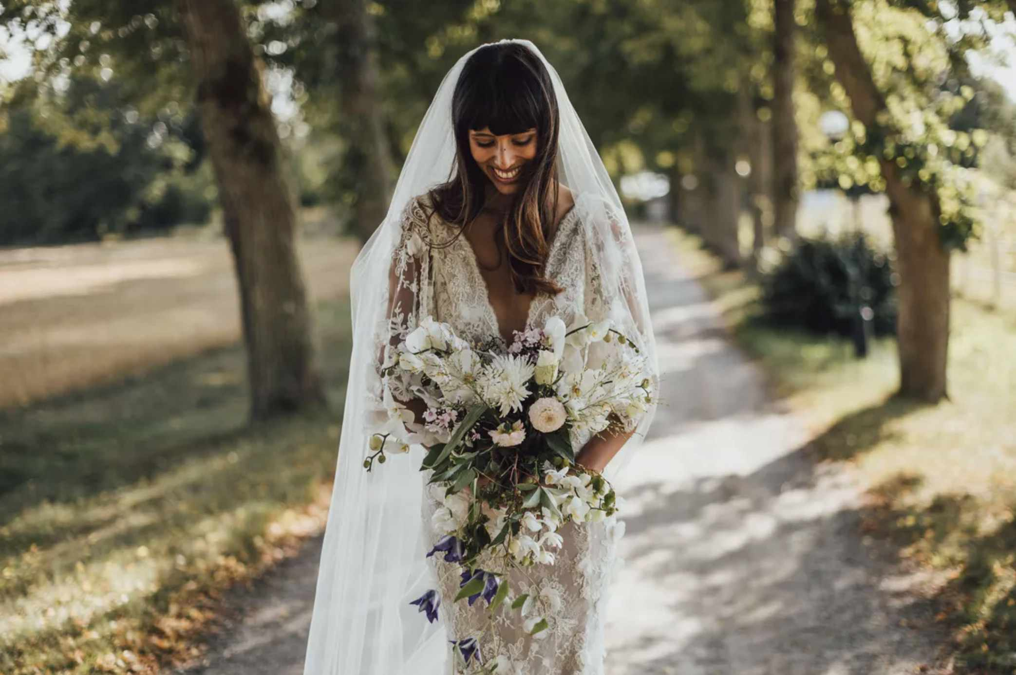Bride with bangs looking at bouquet