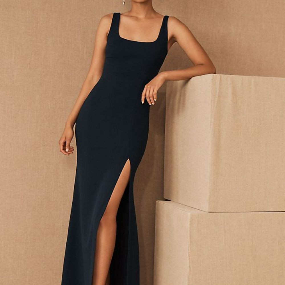 Woman in a square-neck navy blue column dress with a side slit