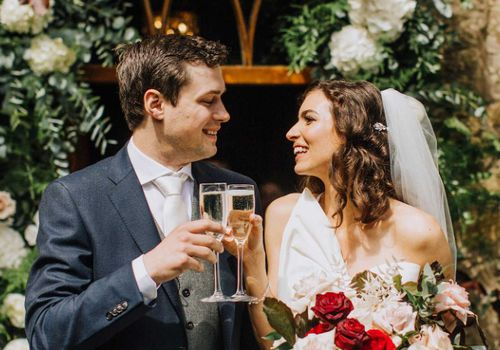 Bride and groom clinking champagne glasses
