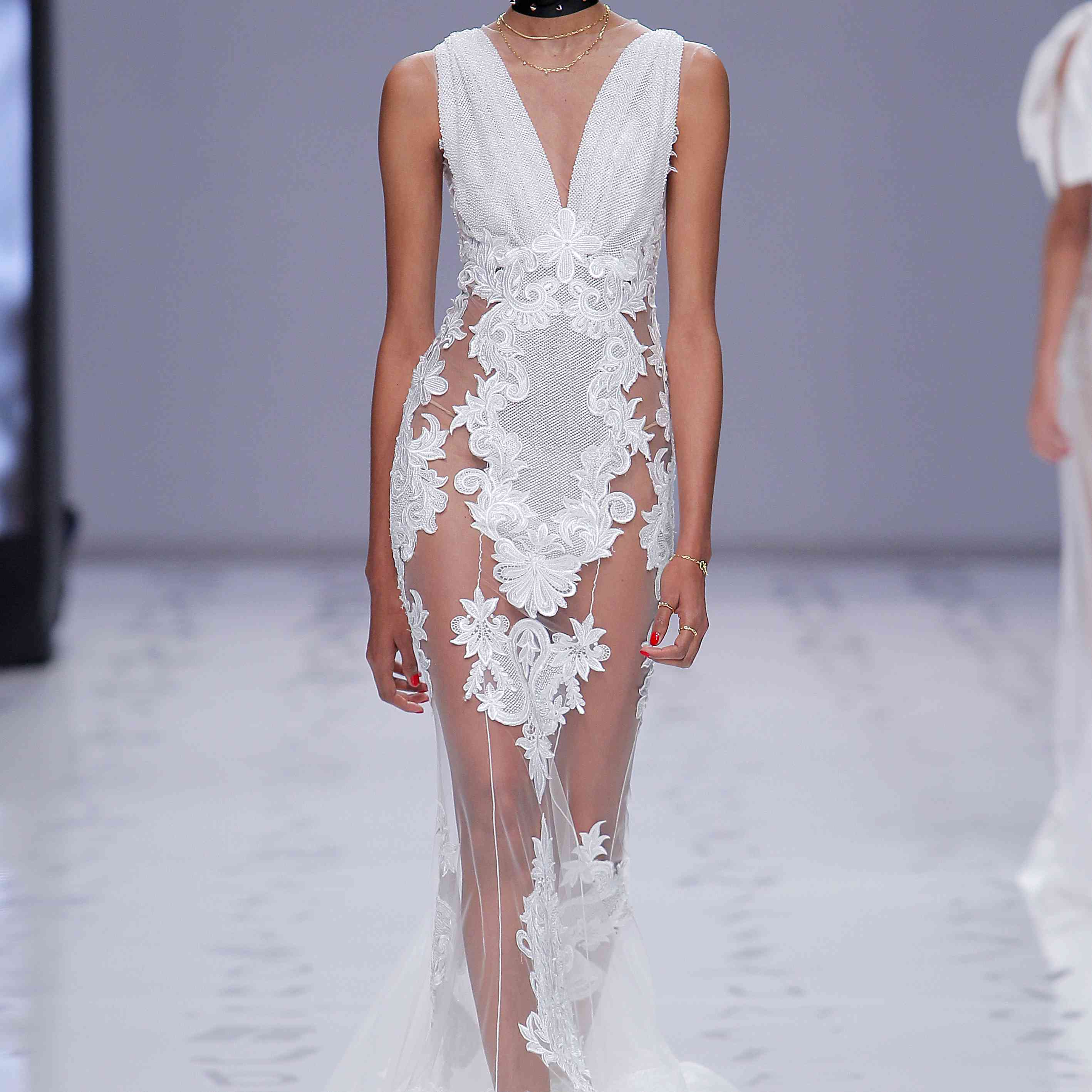 Model in a V-neck sheer tulle mermaid gown with embroidered appliques and glass buttons