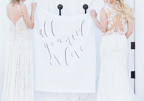 <p>Two Brides with Calligraphed Wedding Sign</p>