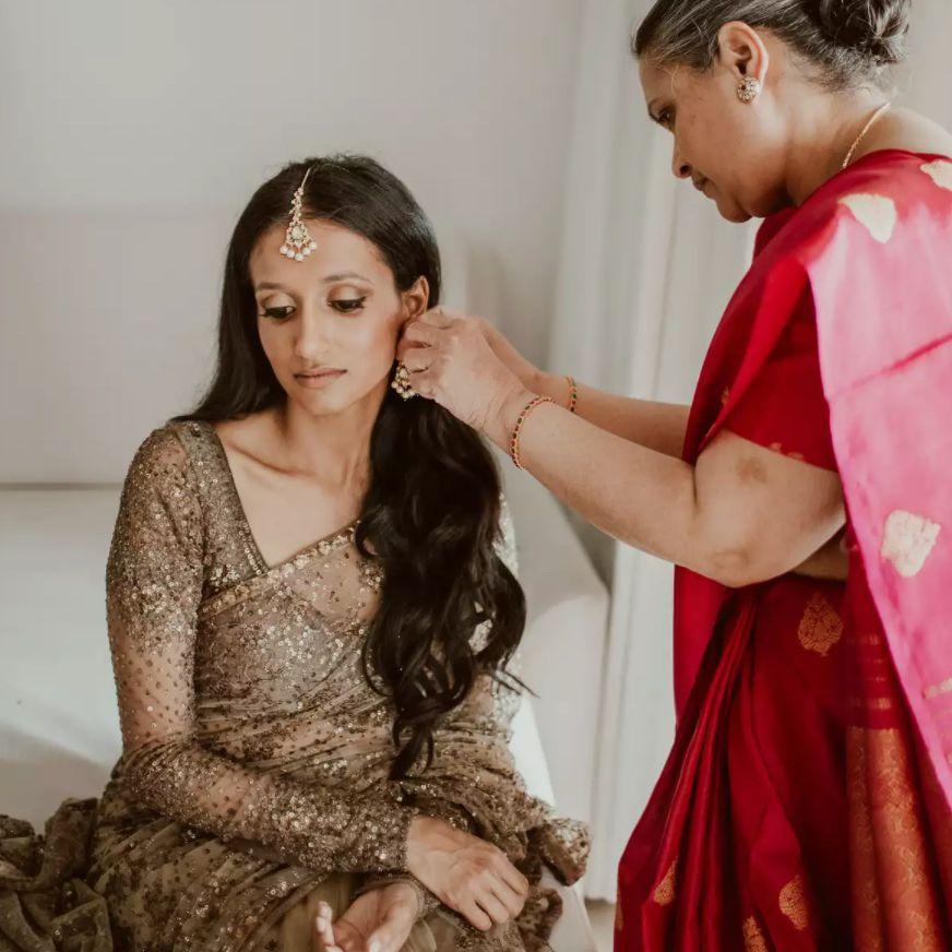 Bride getting help putting earrings in