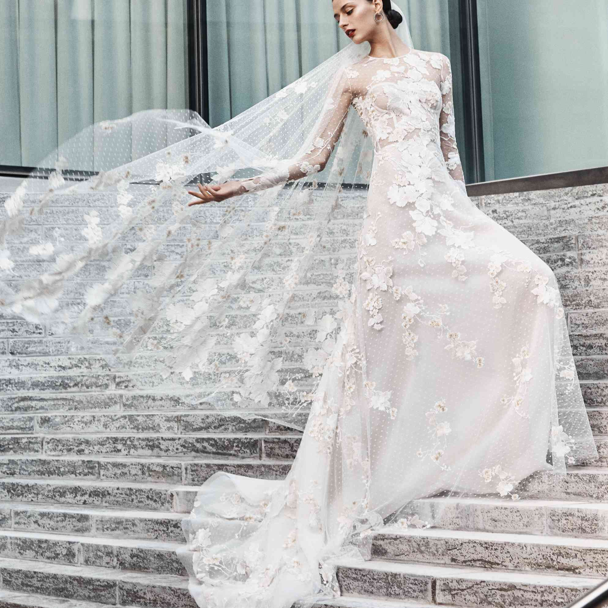 Model on stairs in long-sleeve floral embroidered dress with flowing veil